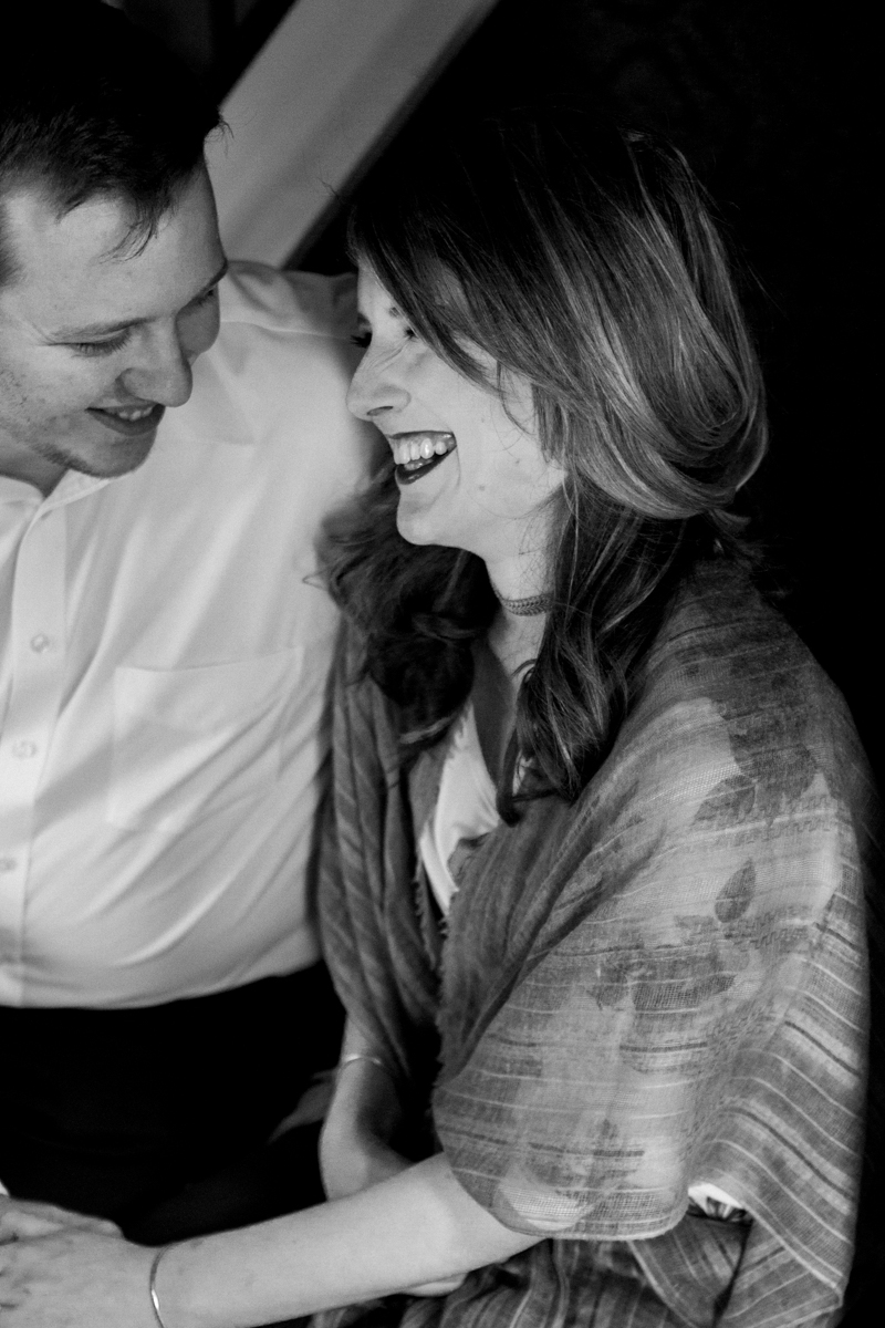 Kansas City lifestyle photographer in home couples session cuddling and laughing on the stairs engagement photos black and white photo