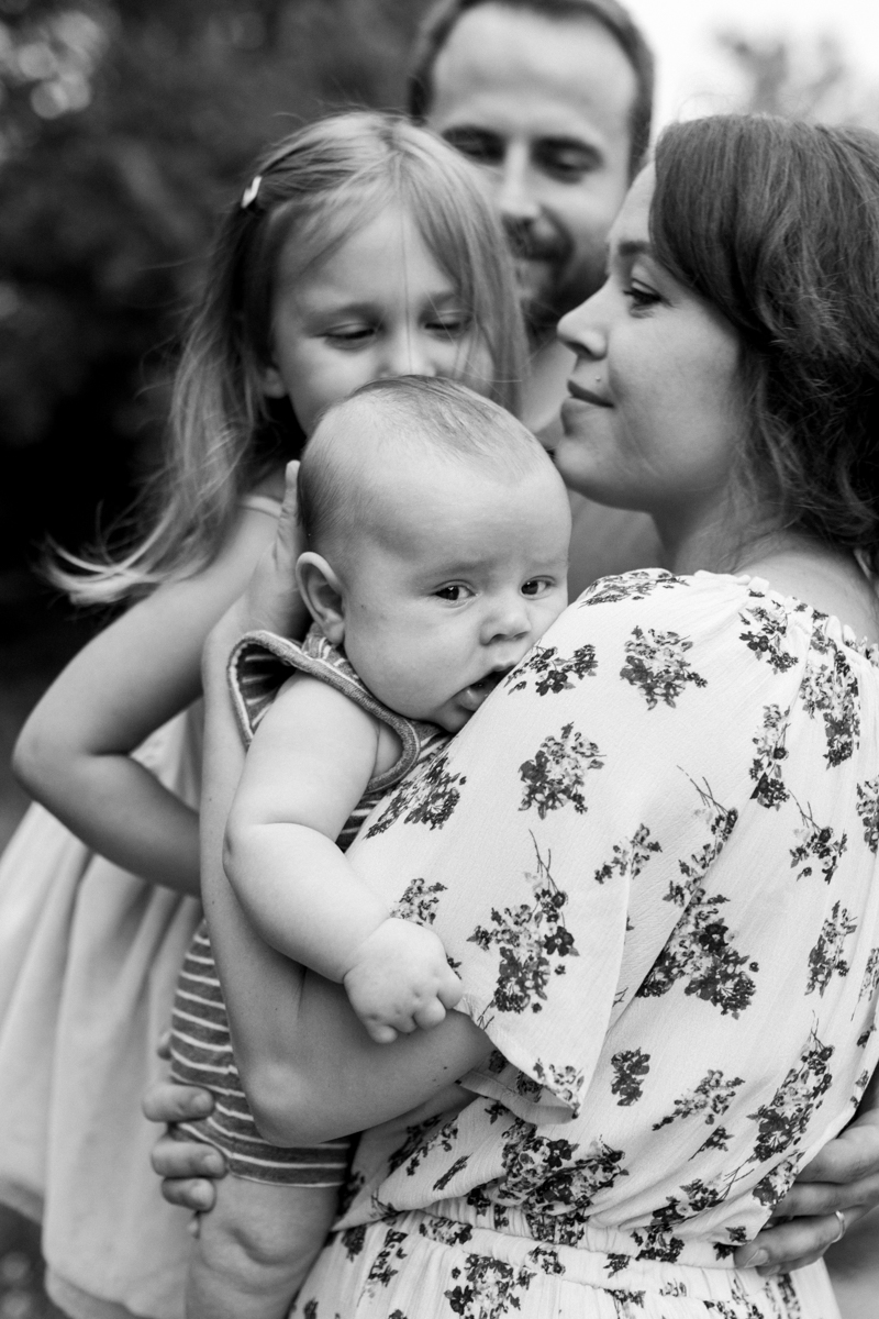 Rebecca Clair Photography Kansas City MO lifestyle family photographer Line Creek Trail Family Session close up of family together and sisters kissing her brother's head black and white photo