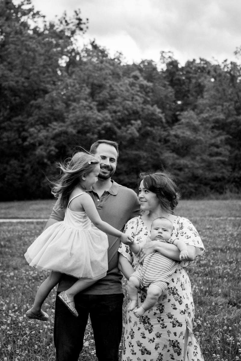 Rebecca Clair Photography Kansas City MO lifestyle family photographer Line Creek Trail Family Session family holding hands under stormy skies black and white photo