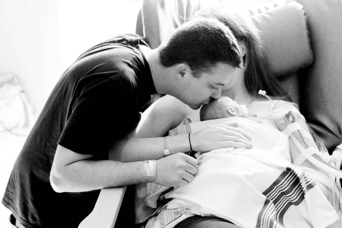 Rebecca Clair Photography lifestyle NICU newborn photography Children's Mercy Hospital dad kissing baby's head black and white photo