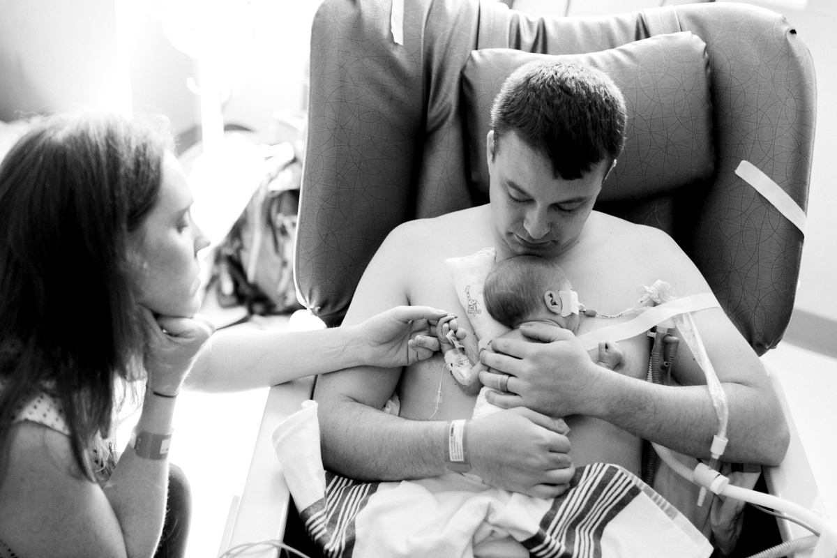 Rebecca Clair Photography lifestyle NICU newborn photography Children's Mercy Hospital father doing skin to skin with his baby mother holding baby's hand  black and white photo