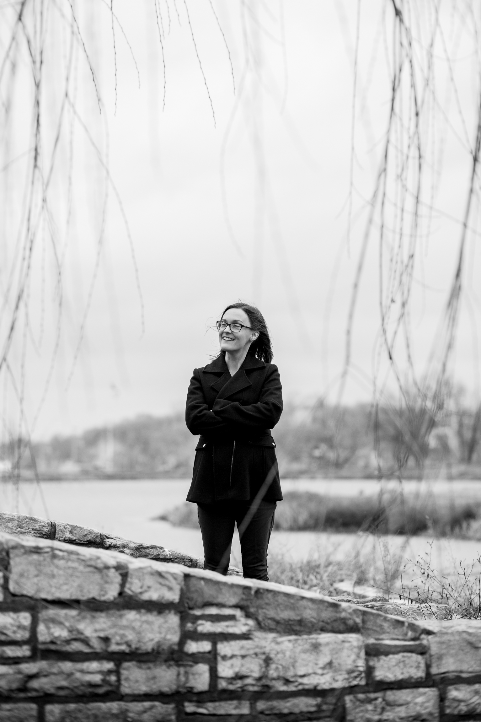 Candid black and white portrait of woman sitting by winter pond, Kansas City lifestyle photographer, Kansas City senior photographer, Kansas City small business headshots, Kansas City lifestyle blogger, candid portrait, winter portrait session, Penn Valley Park
