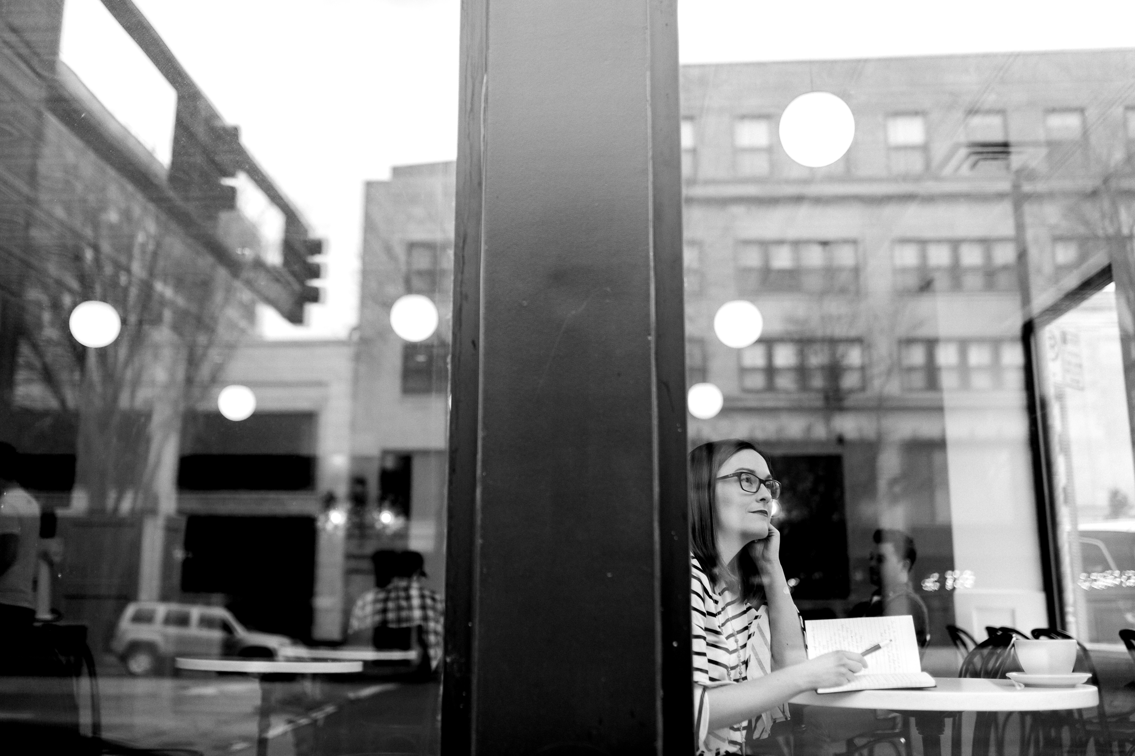 Black and white portrait of a woman thinking through the window of a coffee shop, Kansas City lifestyle photographer, Kansas City senior photographer, Kansas City small business headshots, Kansas City lifestyle blogger, candid portrait, winter portrait session, Monarch Coffee
