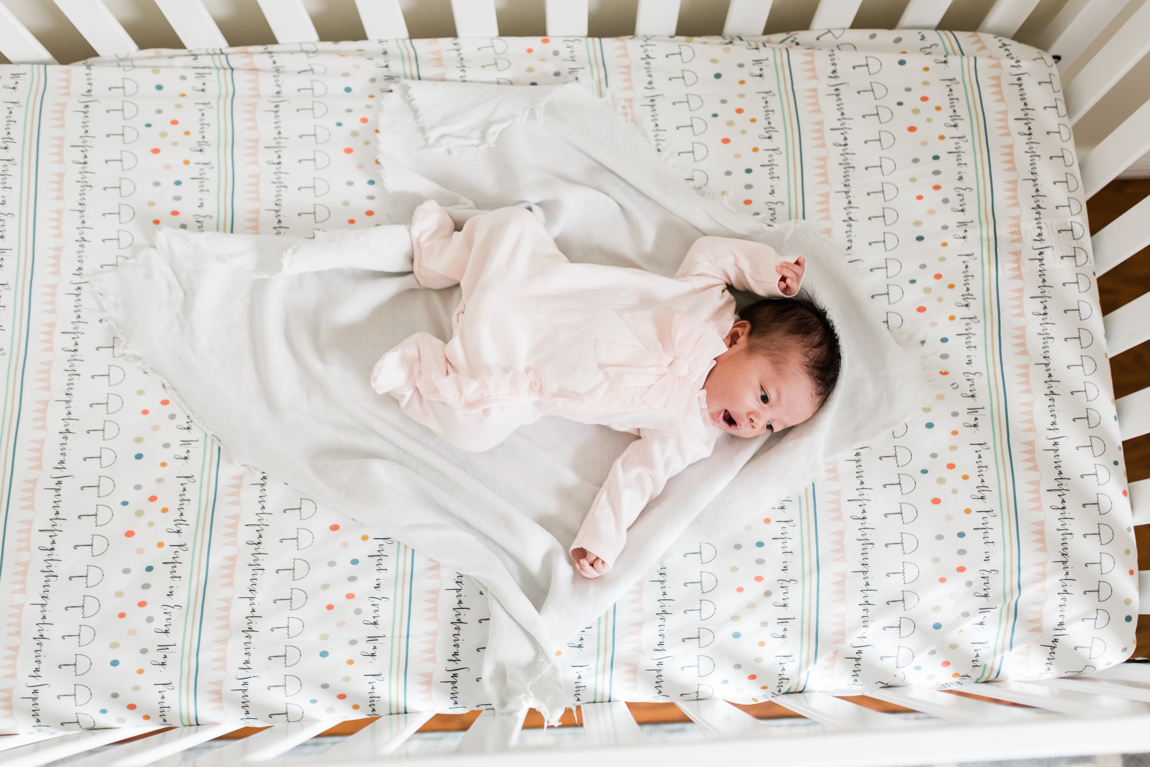 newborn baby in crib, looking down from above, Kansas City lifestyle newborn photographer, in-home newborn session
