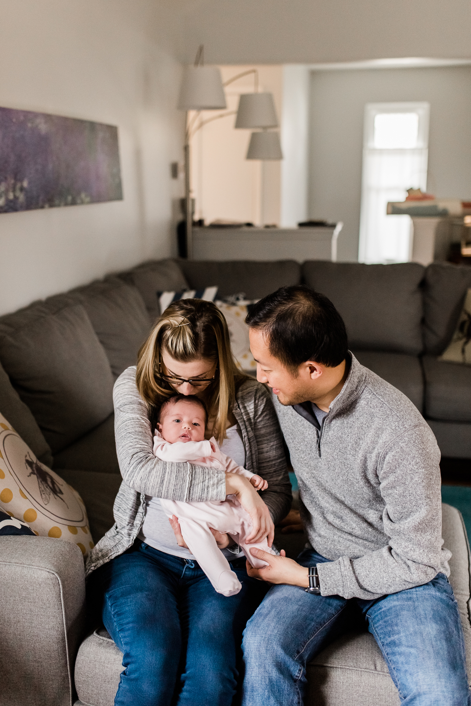 couple holding their newborn baby in the living room, mother kissing her newborn baby's head, Kansas City lifestyle newborn photographer, in-home newborn session