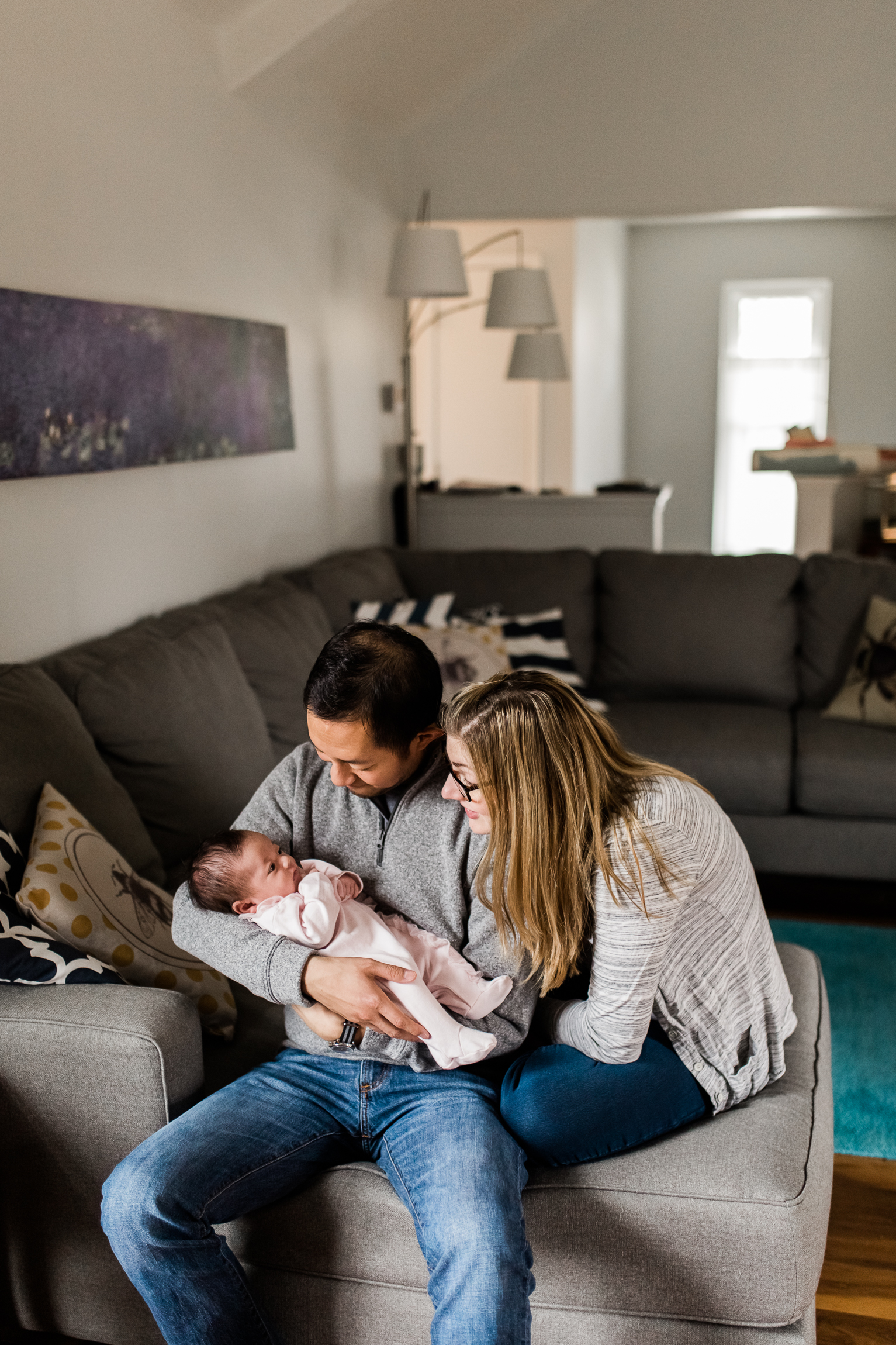 couple holding their newborn baby in the living room, Kansas City lifestyle newborn photographer, in-home newborn session