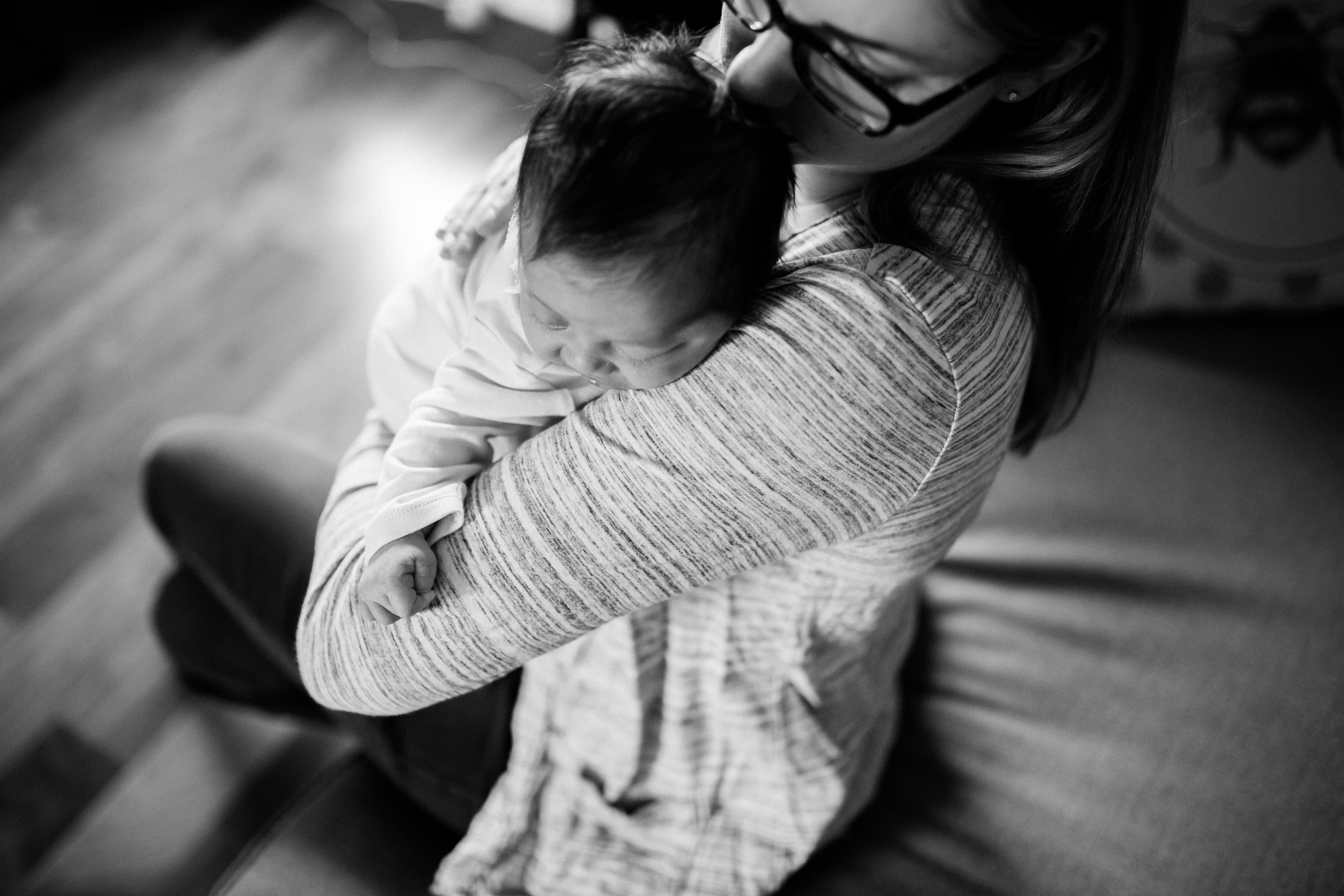 black and white portrait of mother cuddling her newborn daughter, Kansas City lifestyle newborn photographer, in-home newborn session