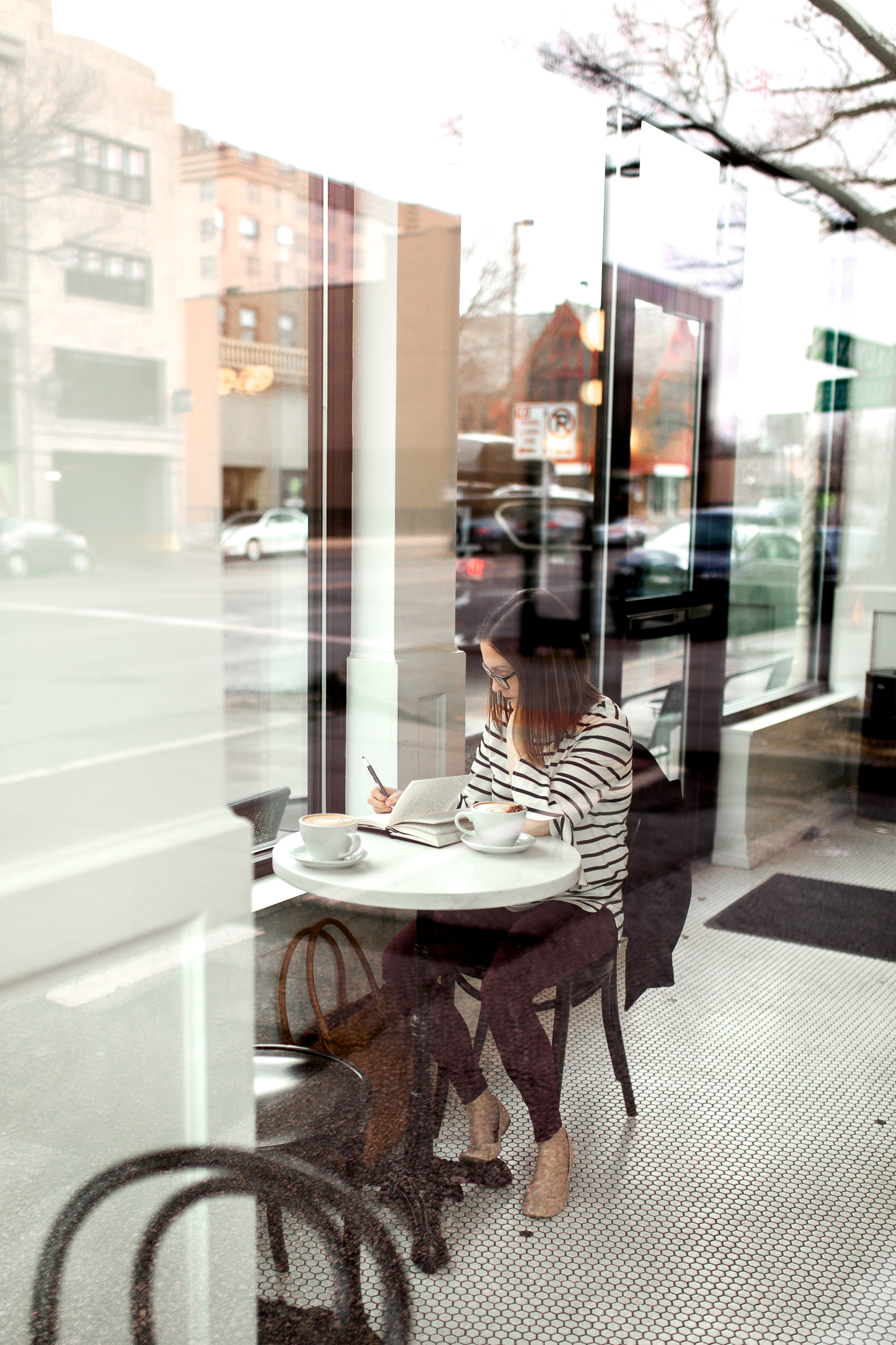Woman writing in a journal through the window of a coffee shop, Kansas City lifestyle photographer, Kansas City senior photographer, Kansas City small business headshots, Kansas City lifestyle blogger, candid portrait, winter portrait session, Monarch Coffee