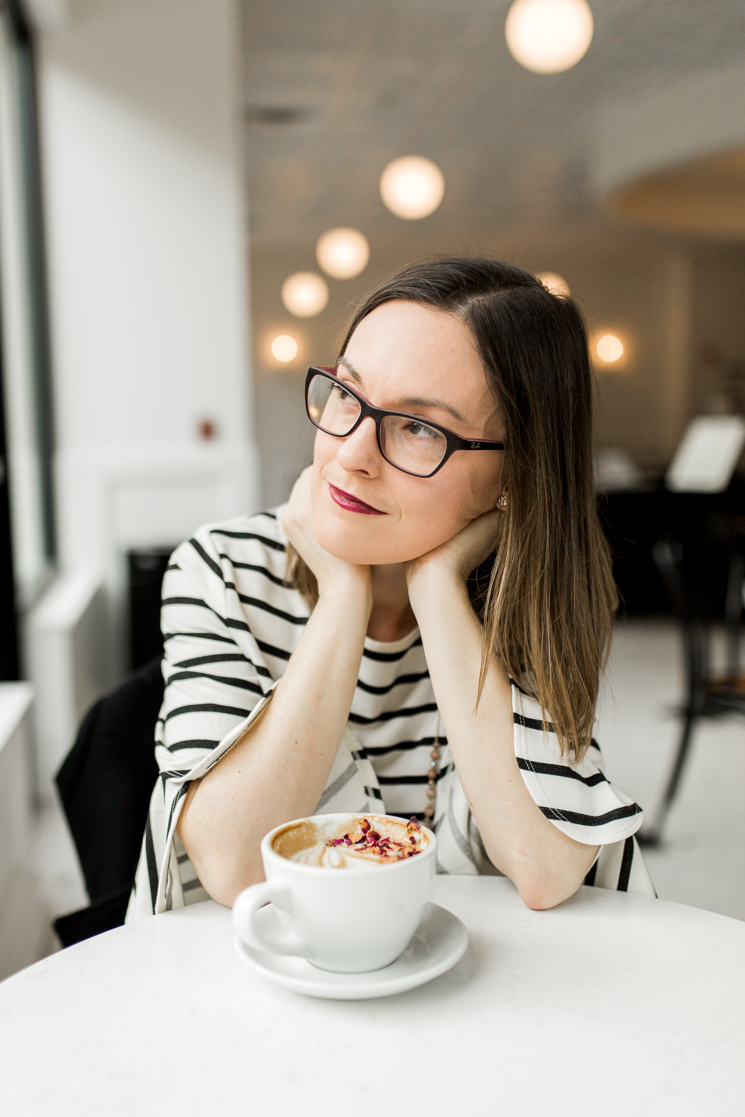 Thoughtful woman with a latte in a coffee shop, Kansas City lifestyle photographer, Kansas City senior photographer, Kansas City small business headshots, Kansas City lifestyle blogger, candid portrait, winter portrait session, Monarch Coffee
