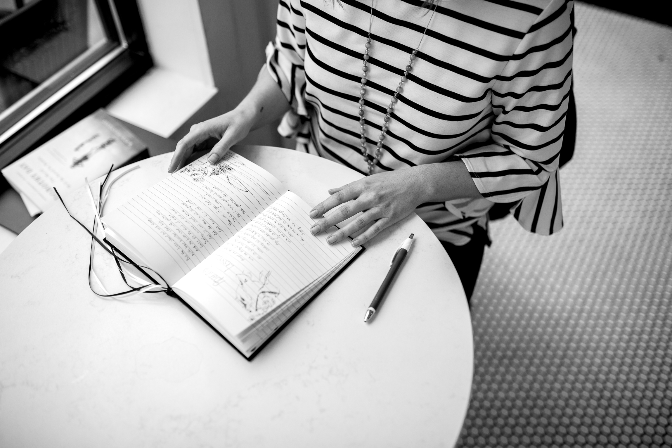 Woman writing in journal in a coffee shop, black and white photo, Kansas City lifestyle photographer, Kansas City senior photographer, Kansas City small business headshots, Kansas City lifestyle blogger, candid portrait, winter portrait session, Monarch Coffee