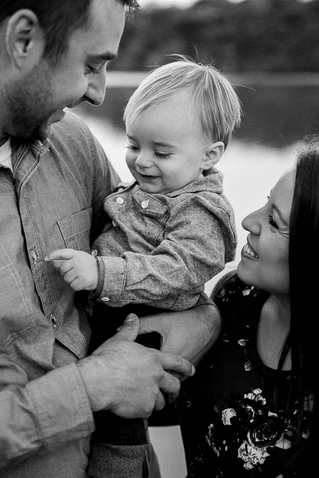 Black and white portrait of parents cuddling their son by the lake, Kansas City lifestyle photographer, sunrise family session at Shawnee Mission Park, Rebecca Clair Photography