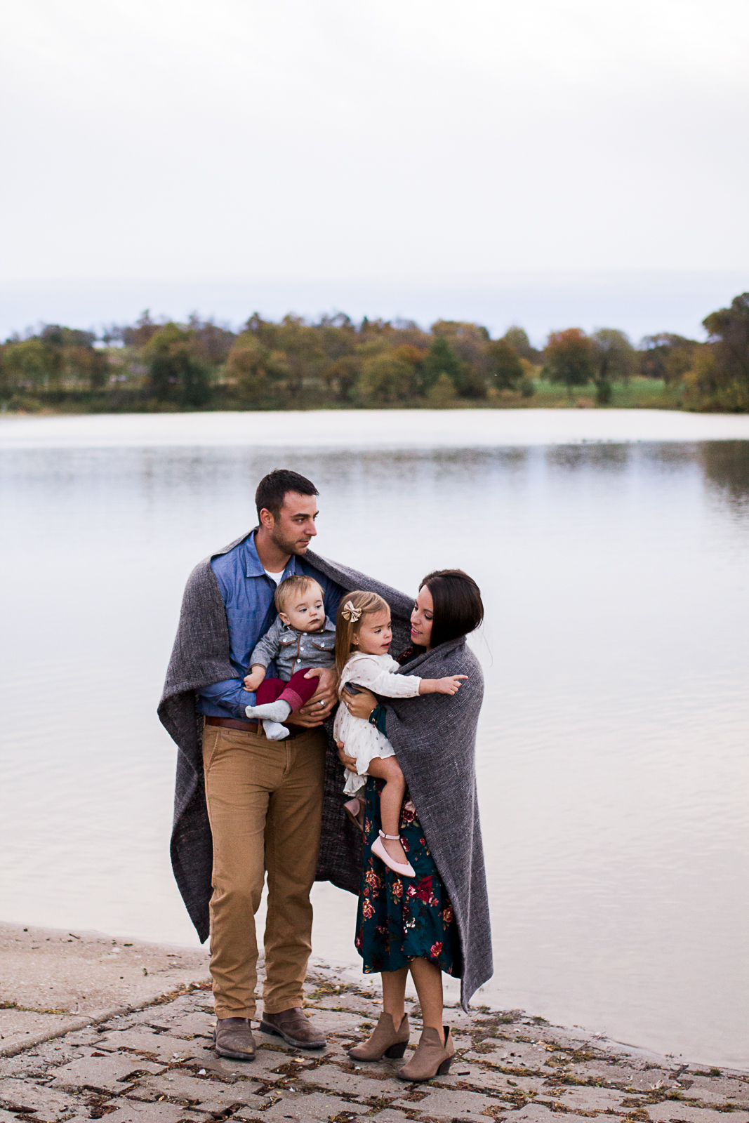 Family portrait wrapped in a blanket by the edge of the lake, sunrise family session at Shawnee Mission Park, Rebecca Clair Photography