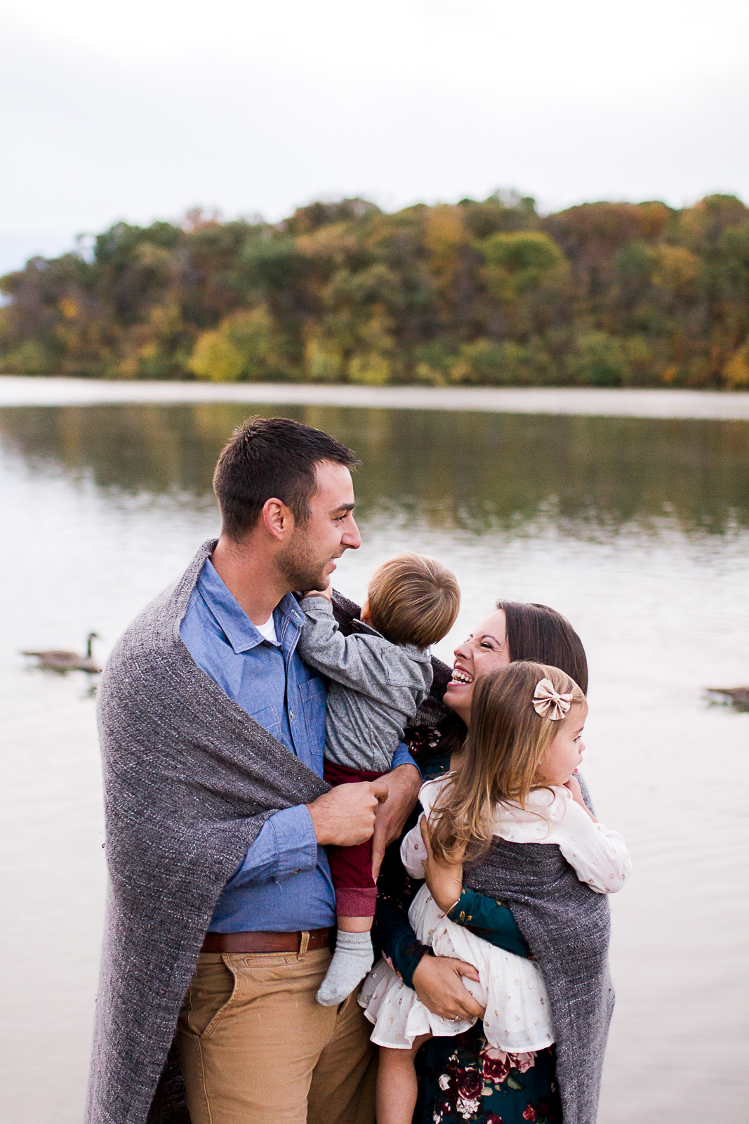 Candid photo of a family cuddling in a blanket by a lake, Kansas City family photographer, autumn family session at Shawnee Mission Park, Rebecca Clair Photography
