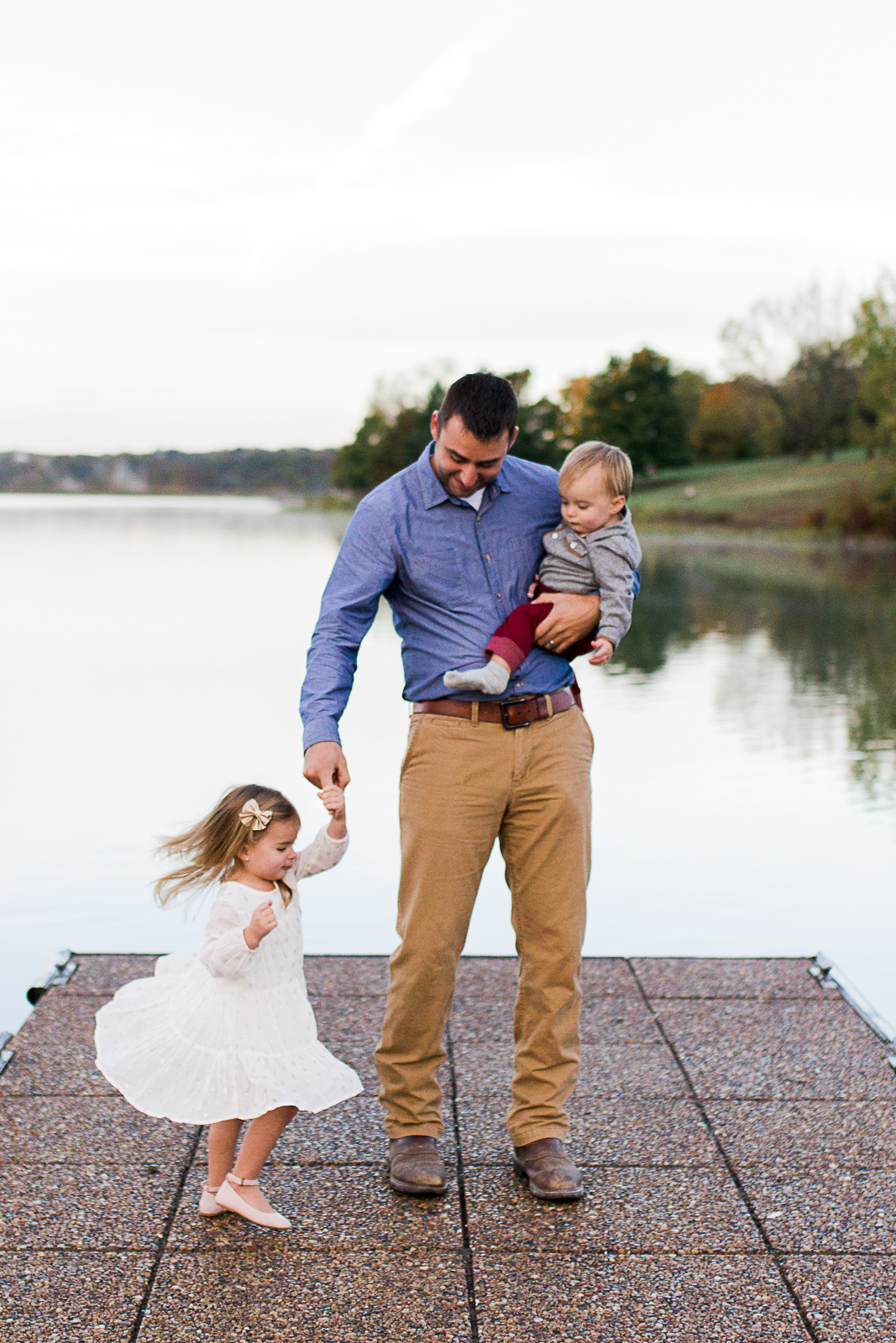 Father dances with his daughter on a dock, Kansas City family photographer, sunrise family session at Shawnee Mission Park, Rebecca Clair Photography