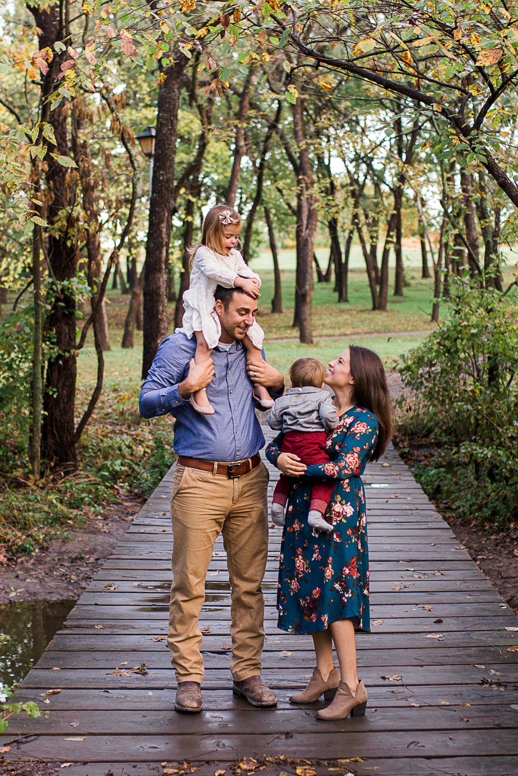 Daughter sits on dads shoulders and family stands in the woods, fall family photos, Shawnee Mission Park sunrise session, Rebecca Clair Photography