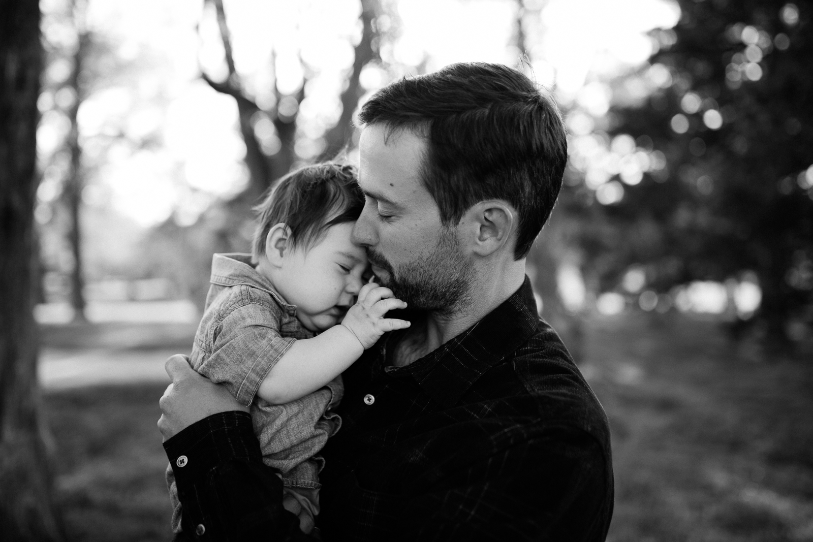 Black and white portrait of father cuddling his son, emotive portrait of father and son, Kansas City family photographer, Rebecca Clair Photography
