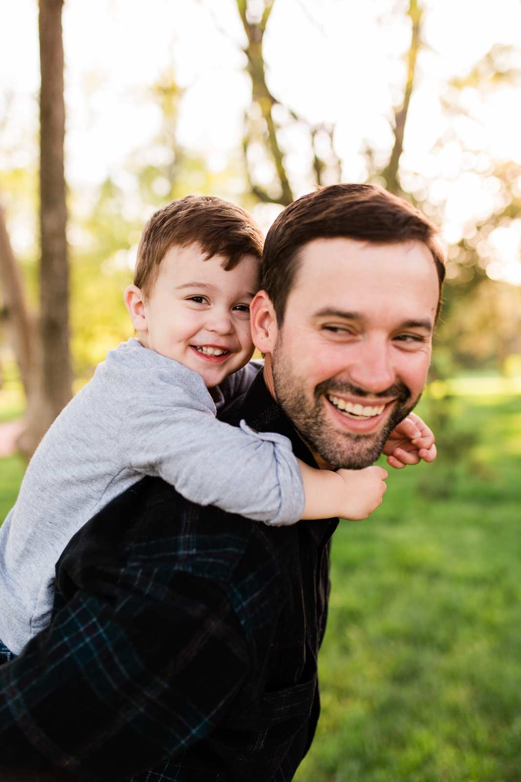 Father gives his son a piggyback ride in the park, Kansas City family photographer, Rebecca Clair Photography