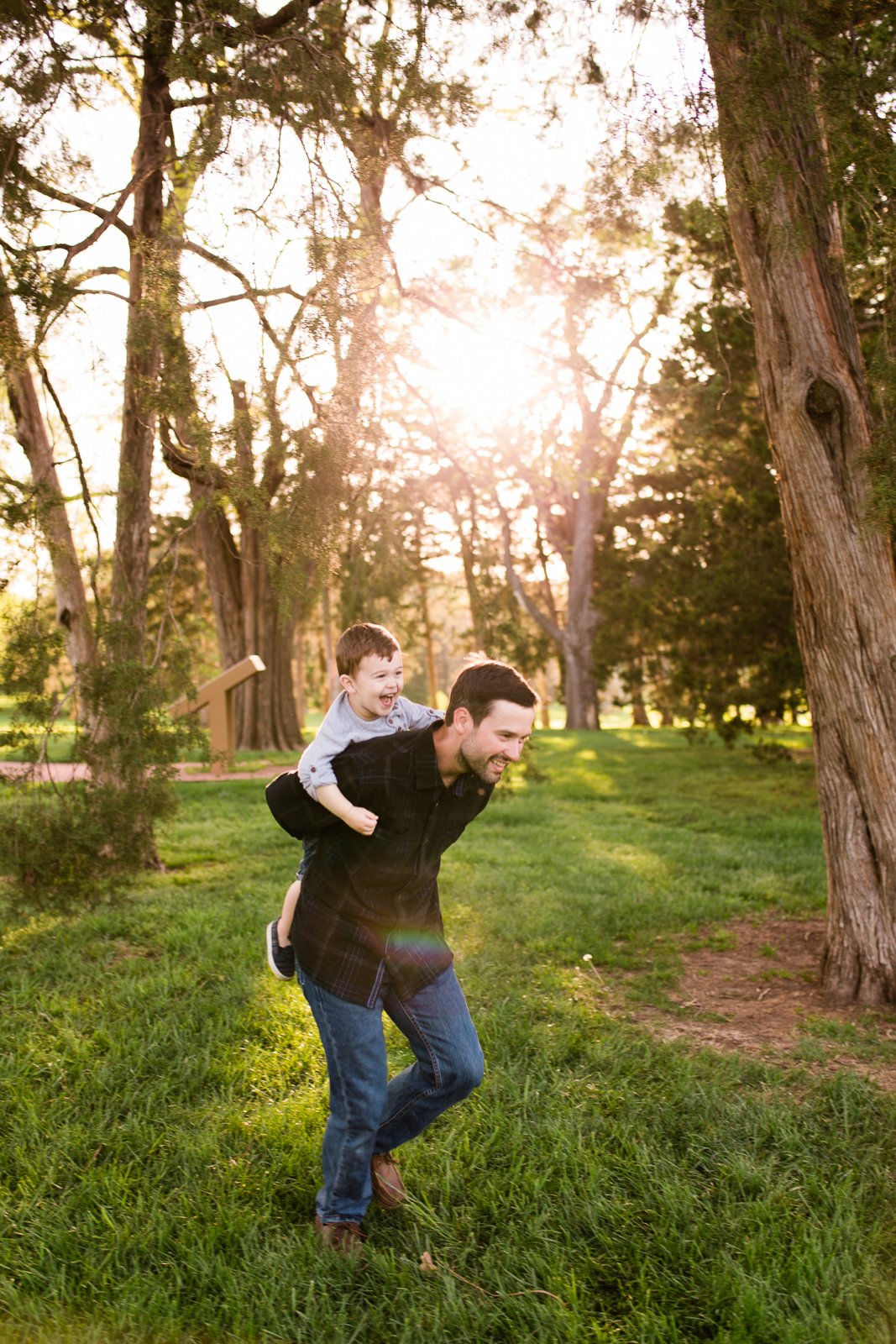 Father gives his son a piggyback ride in the park, Loose Park golden hour session, Kansas City lifestyle photographer, Rebecca Clair Photography