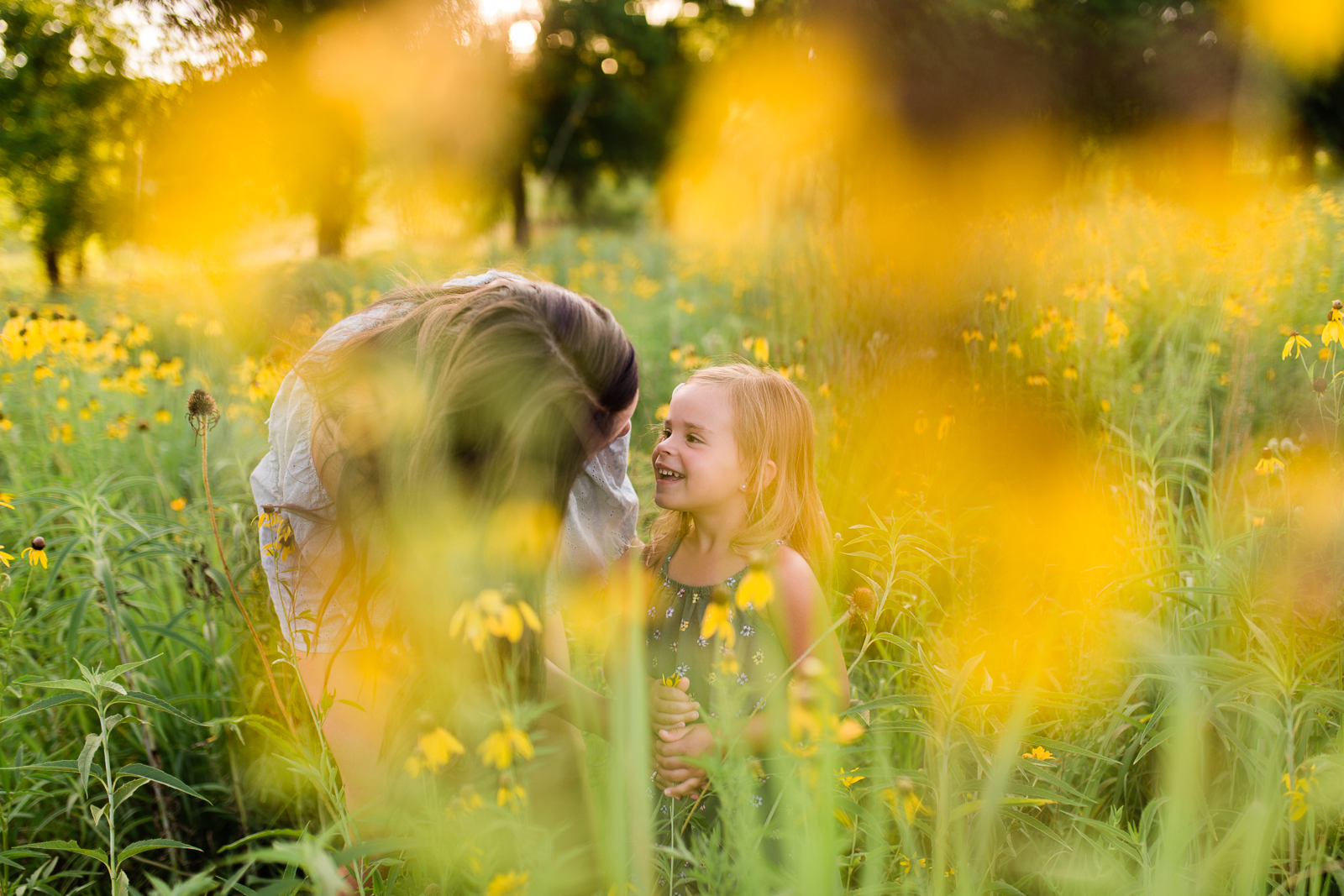 Mother talks to her daughter in a field of flowers, mommy and me session at Shawnee Mission Park, Kansas City lifestyle photographer