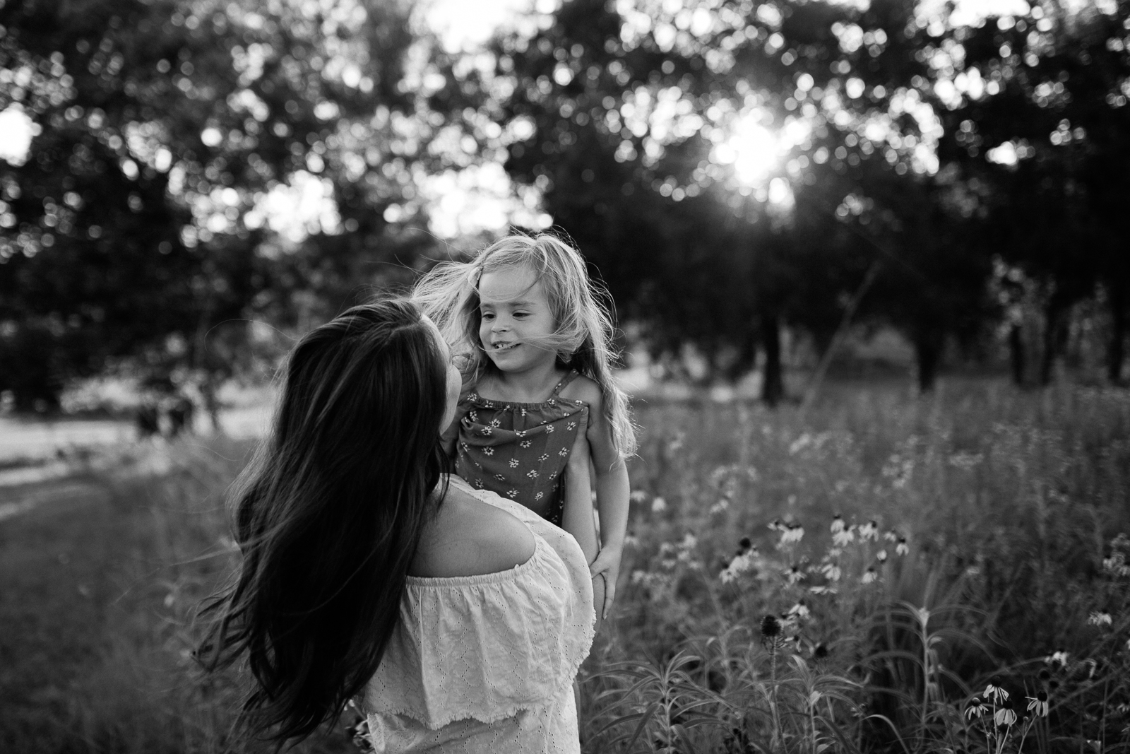 Black and white photo of mother lifting daughter, windswept portrait, mommy and me session at Shawnee Mission Park, Kansas City family photographer