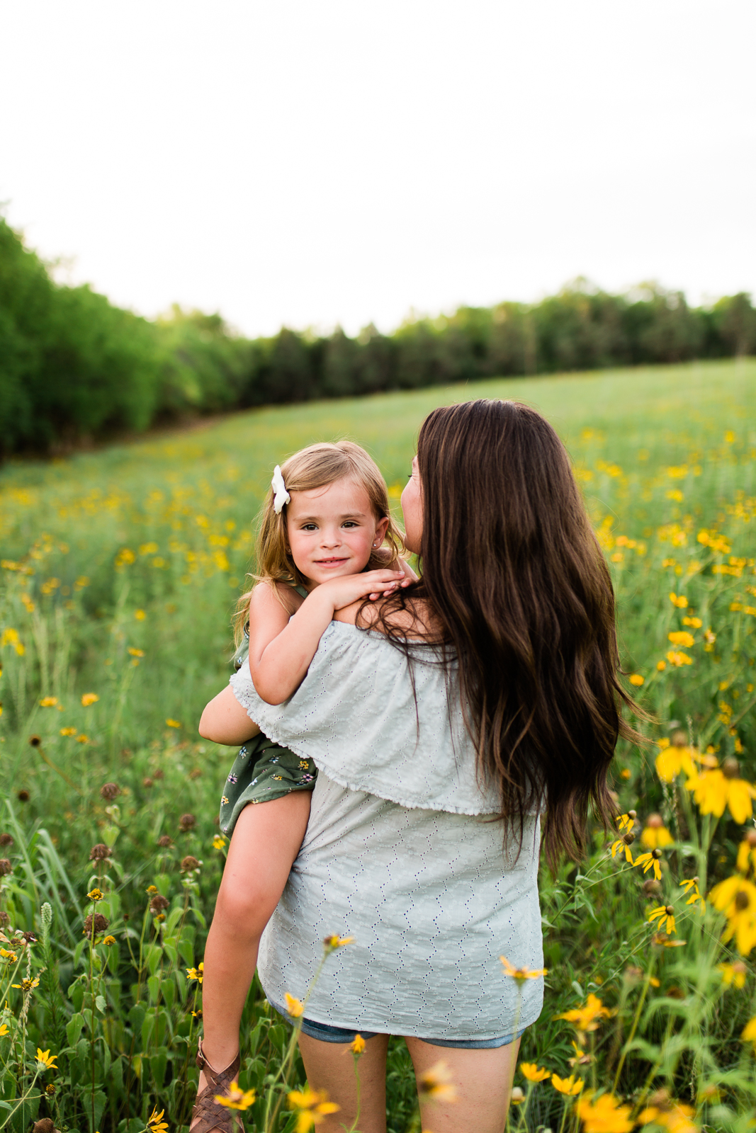 Mother carries daughter into a field of flowers, mommy and me session at Shawnee Mission Park, Kansas City family photographer