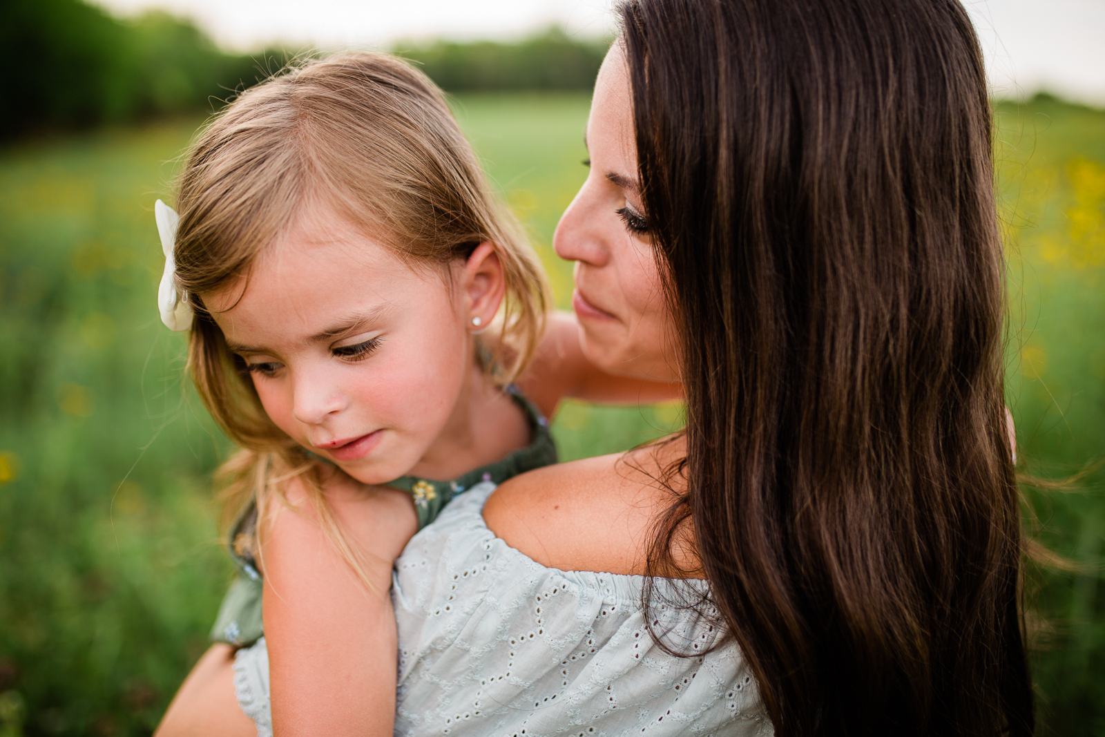 Mother holds daughter in a field, mommy and me session at Shawnee Mission Park, Kansas City family photographer