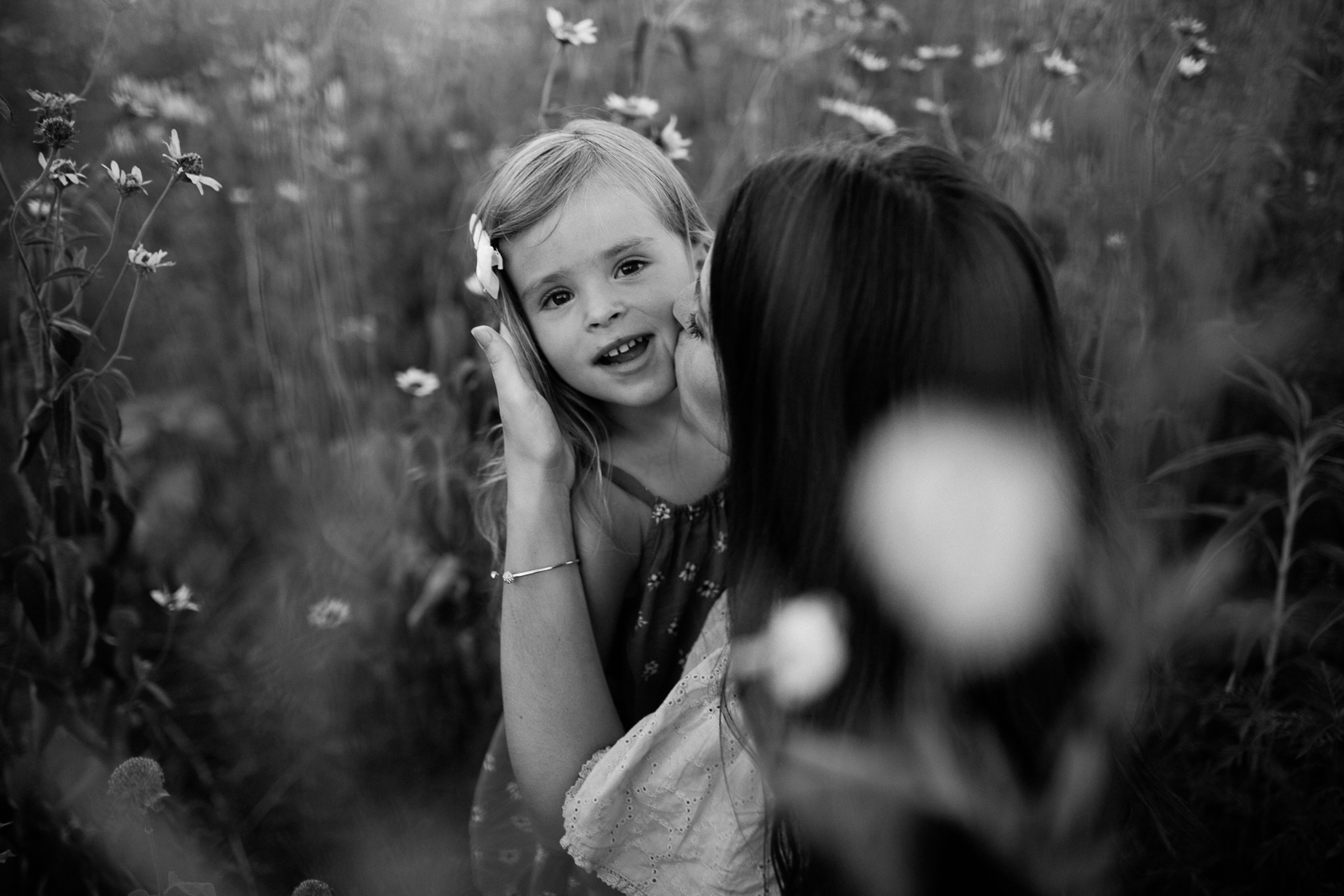 Black and white photo of mother kissing her daughter in a field of flowers, mommy and me session at Shawnee Mission Park, Kansas City family portrait photographer