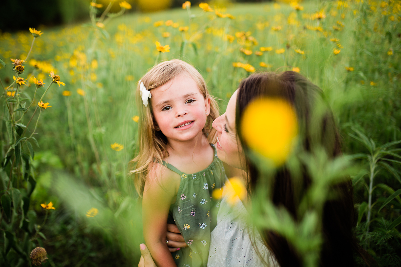 Mother and daughter cuddle in a field of flowers, mommy and me session at Shawnee Mission Park, Kansas City family photographer