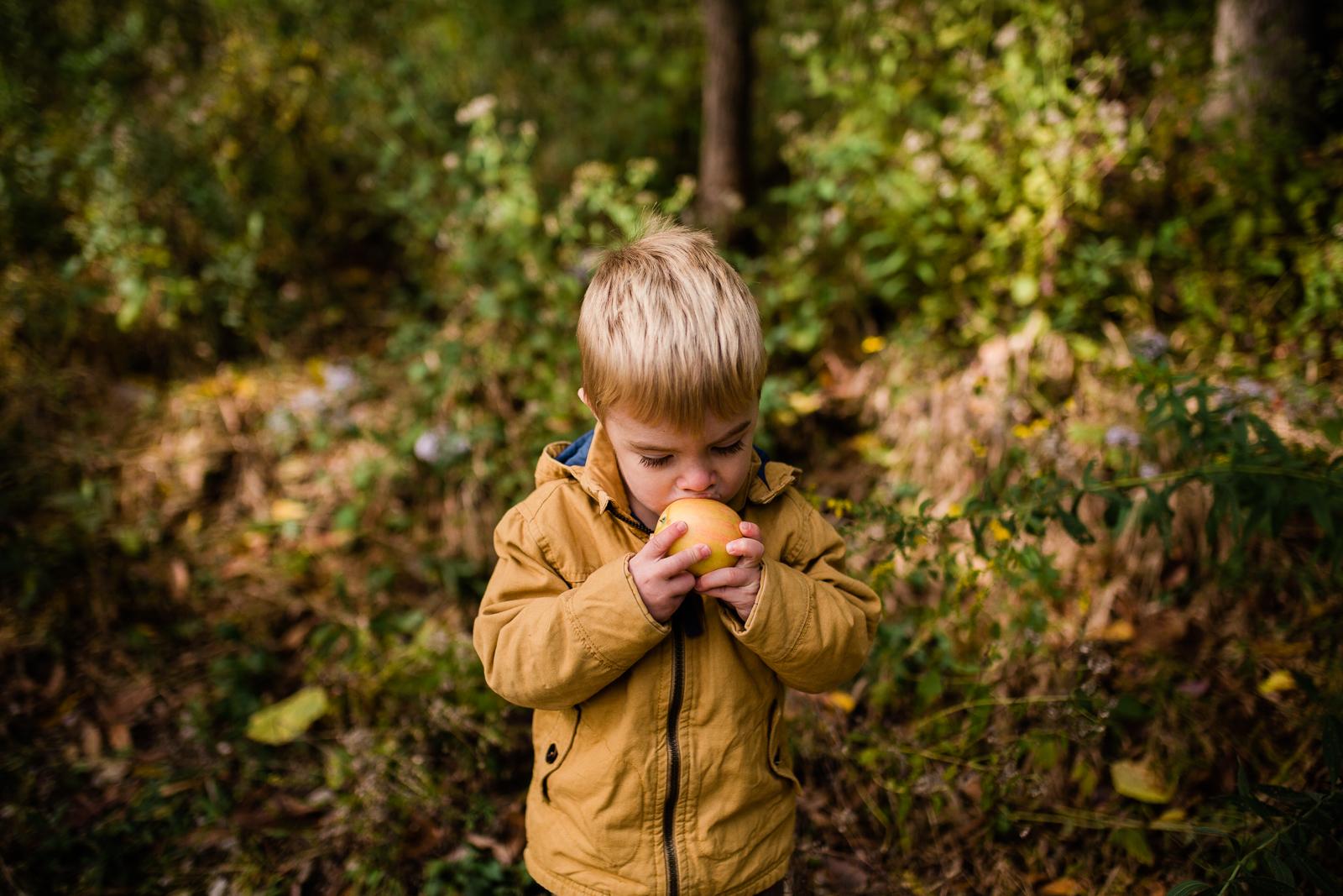 Little boy eats apple in the woods, Kansas City lifestyle photographer, Lakeside Nature Center