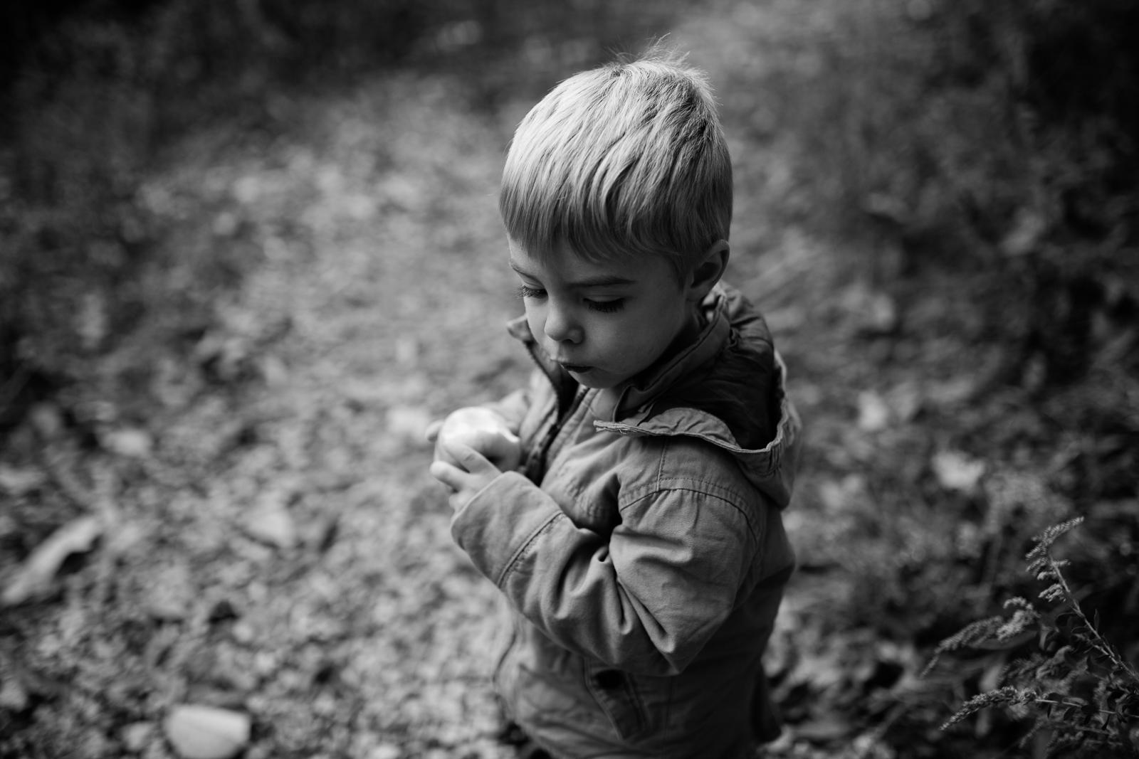 Black and white photo of boy eating apple, moody fall photos, Kansas City photographer