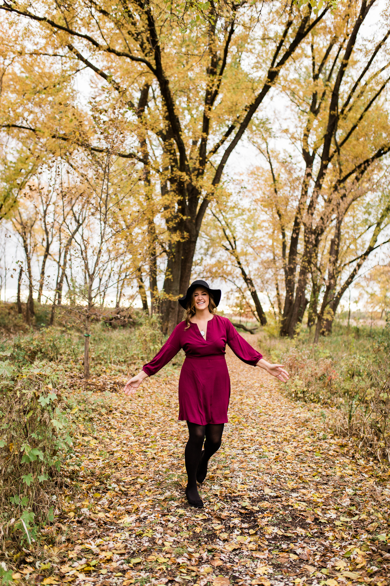 Woman dances in the autumn woods, carefree lifestyle branding images, Kansas City lifestyle coach, Rebecca Clair Photography