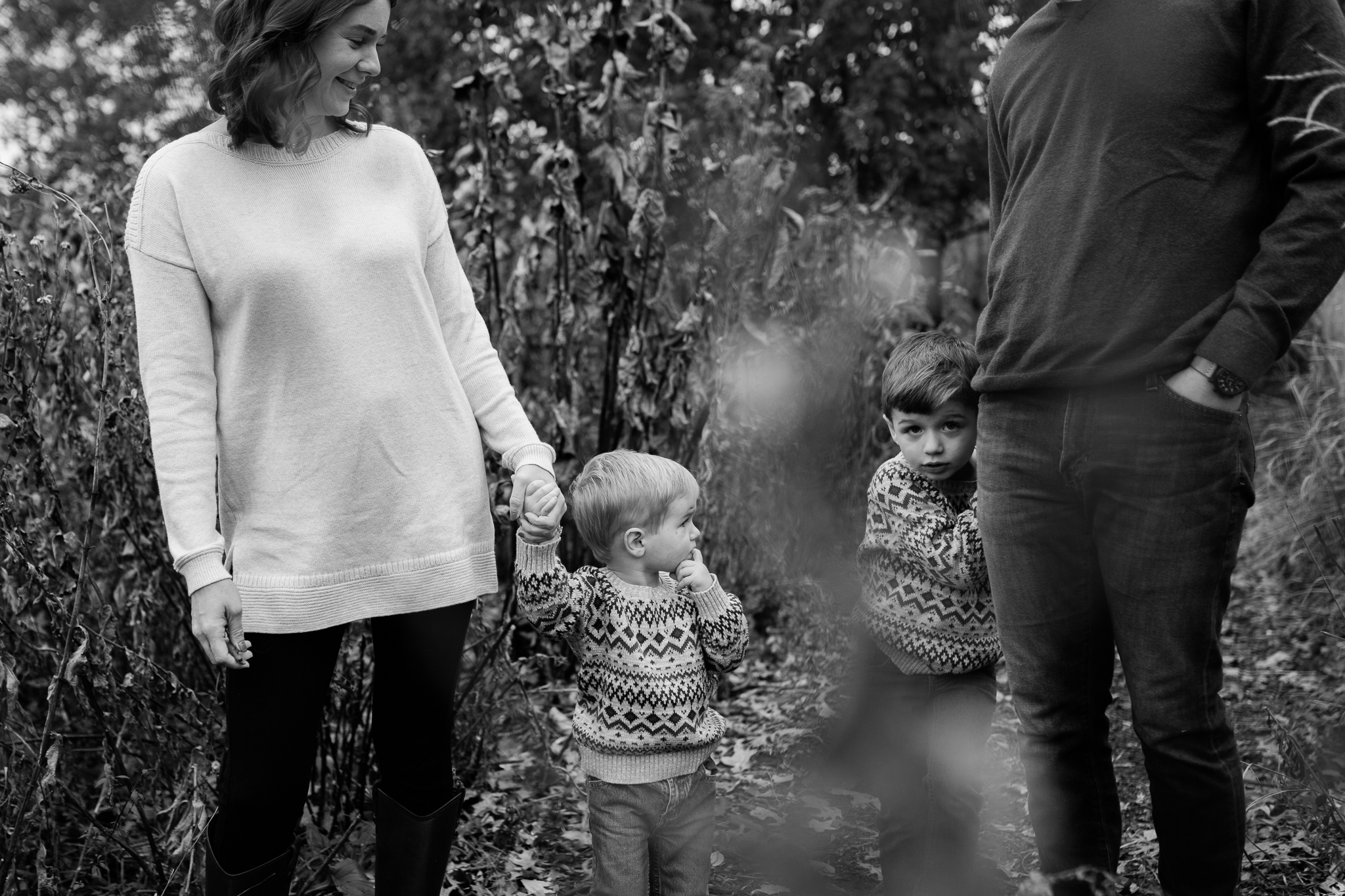 Family walks through a field, son peeks out from his father's leg, Kansas City lifestyle family photos, Rebecca Clair Photography
