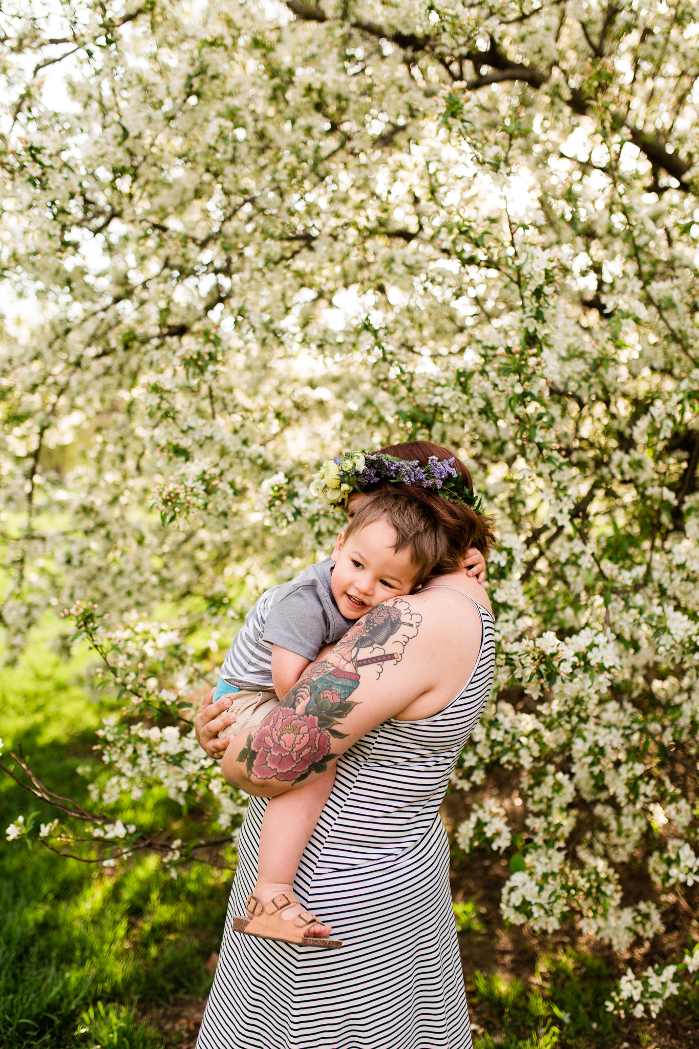 Mother holds her toddler son by the flowering trees, Kansas City spring mini sessions, Loose Park, Rebecca Clair Photography
