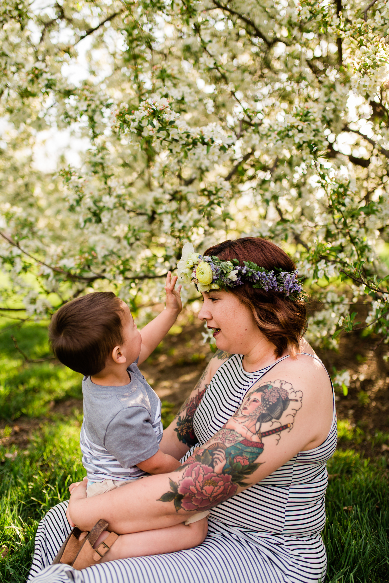 Little boy touches his mother's flower crown, spring mommy and me mini session at Loose Park, Rebecca Clair Photography