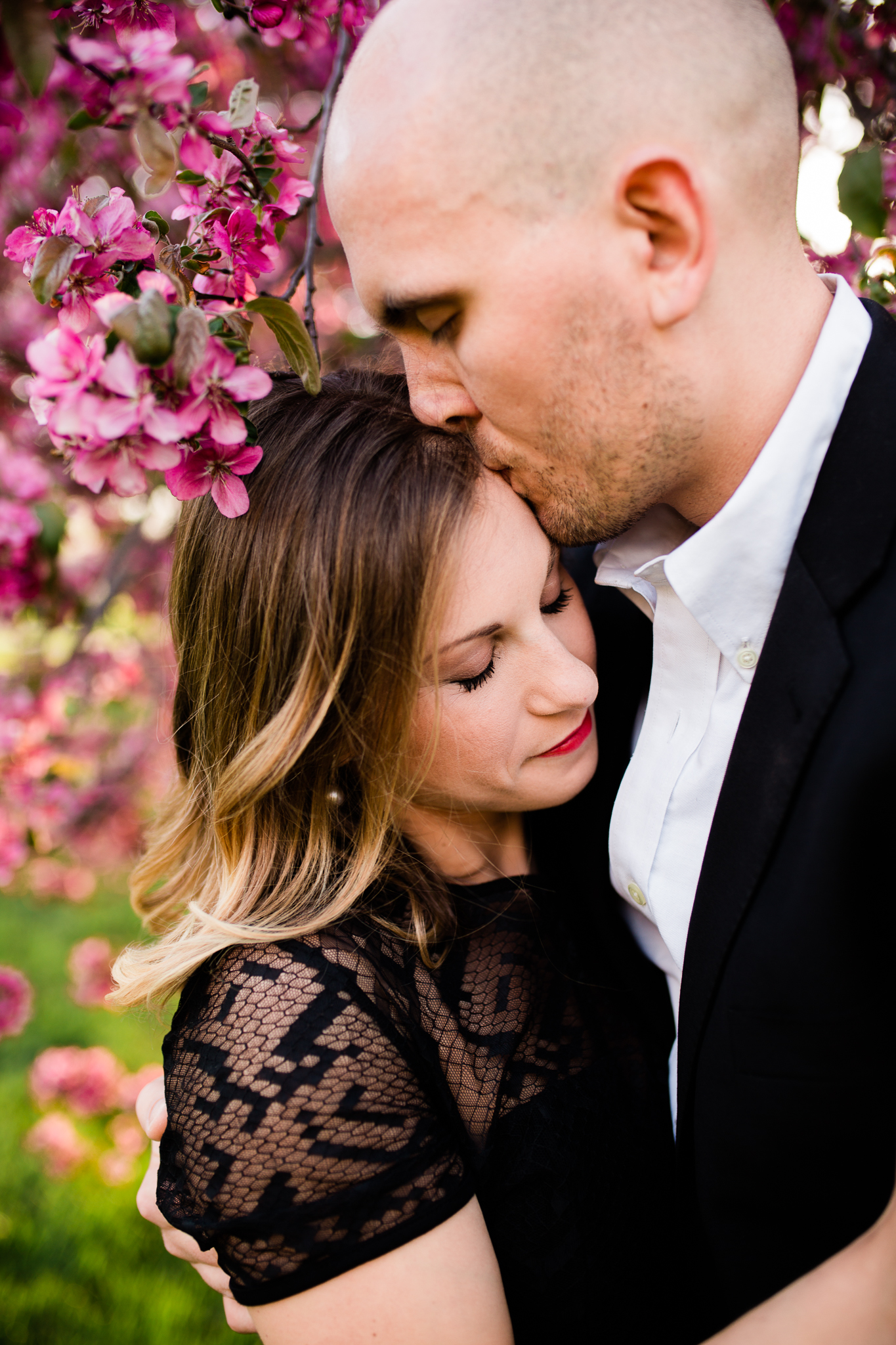 Man kisses his fiance's forehead under the apple blossoms, Kansas City emotive engagment photography, Rebecca Clair Photography