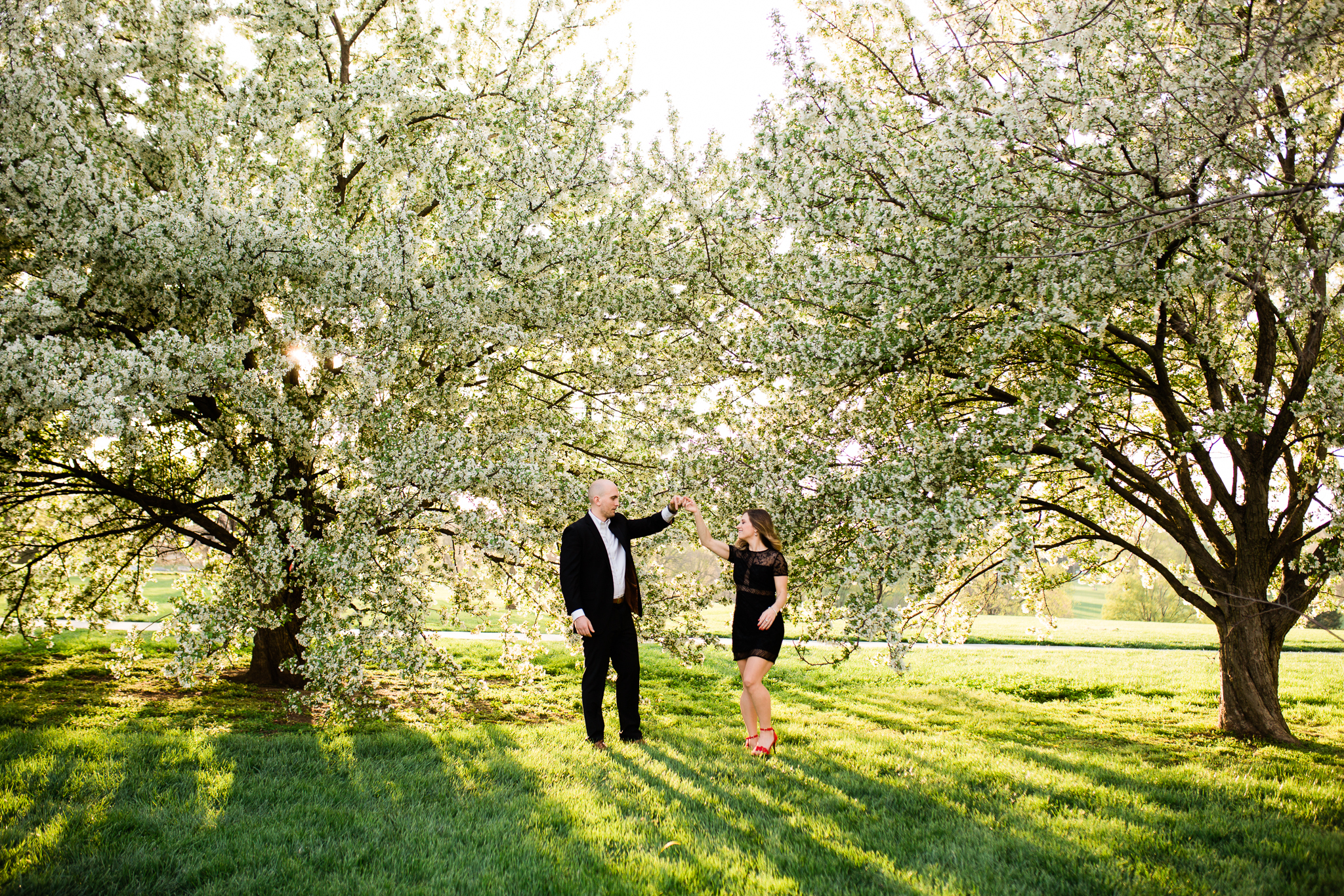Couple dances under the flowering apple trees, Loose Park in the spring, Kansas City couples session, Rebecca Clair Photography