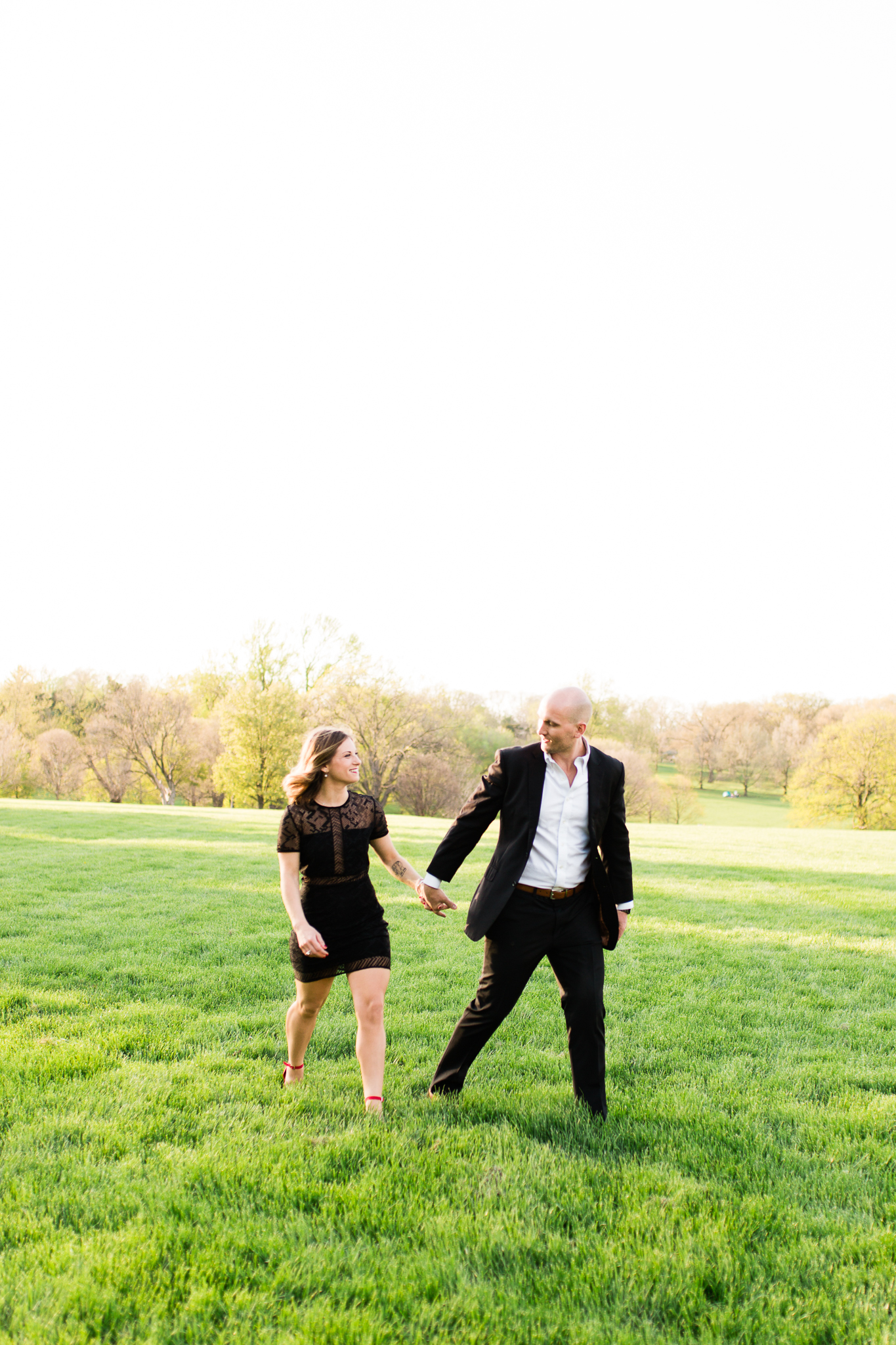 Formal couple walks across an open field, Loose Park couples session, Rebecca Clair Photography