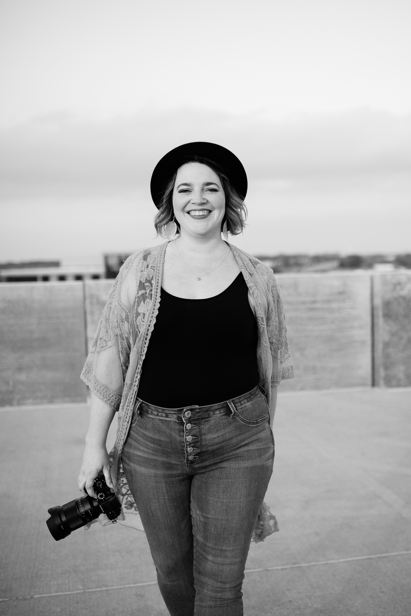 Black and white portrait of photographer walking across a rooftop, Kansas City natural headshots, Rebecca Clair Photography