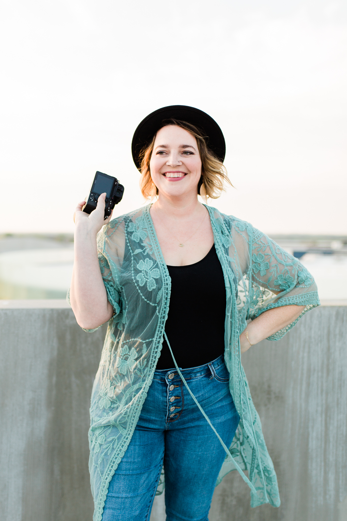 Photographer laughs on a rooftop at sunset, Kansas City candid portrait photographer, Rebecca Clair Photography