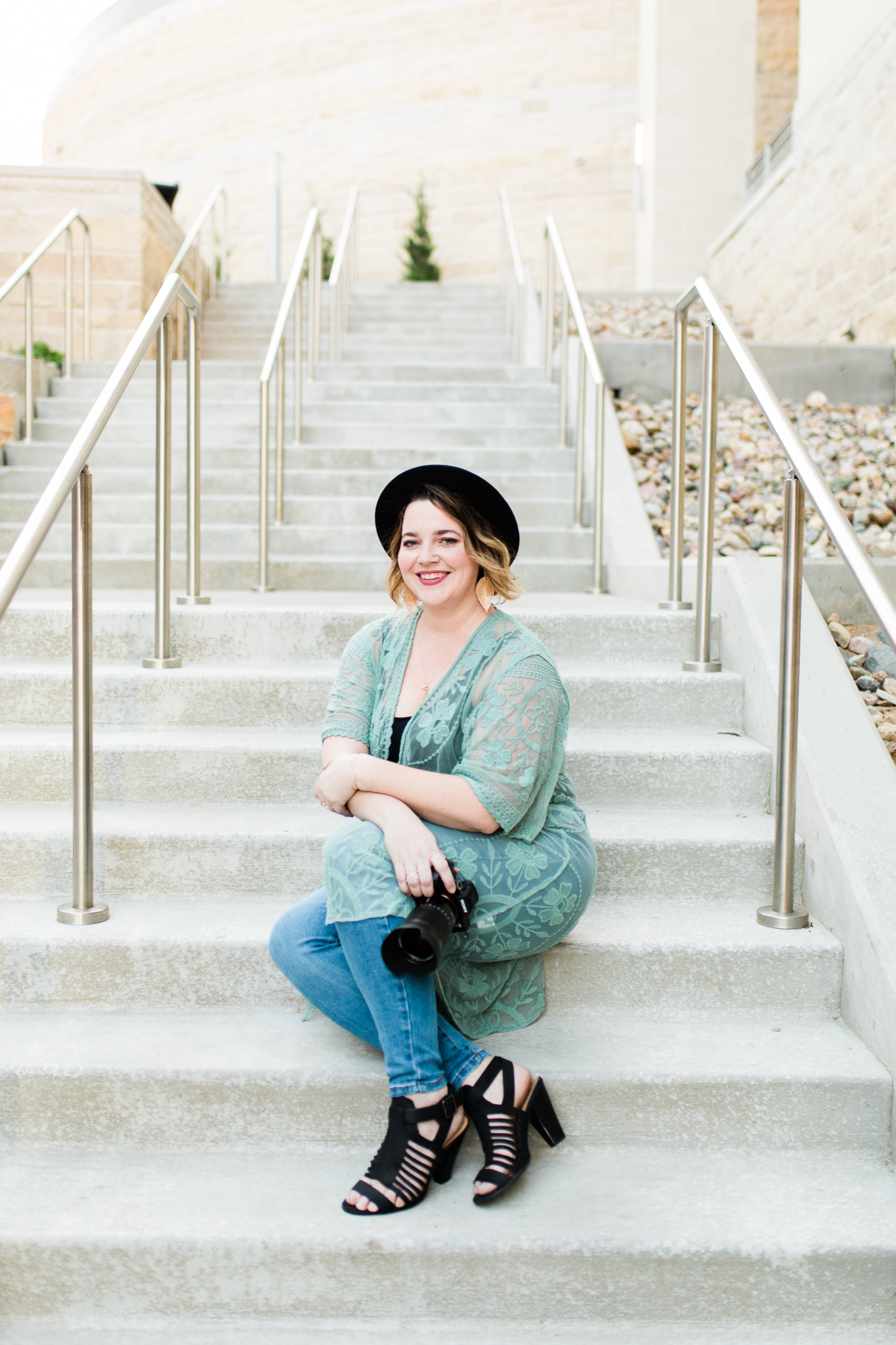 Photographer sits on the steps with ehr camera, Kansas City small business headshots, Rebecca Clair Photography