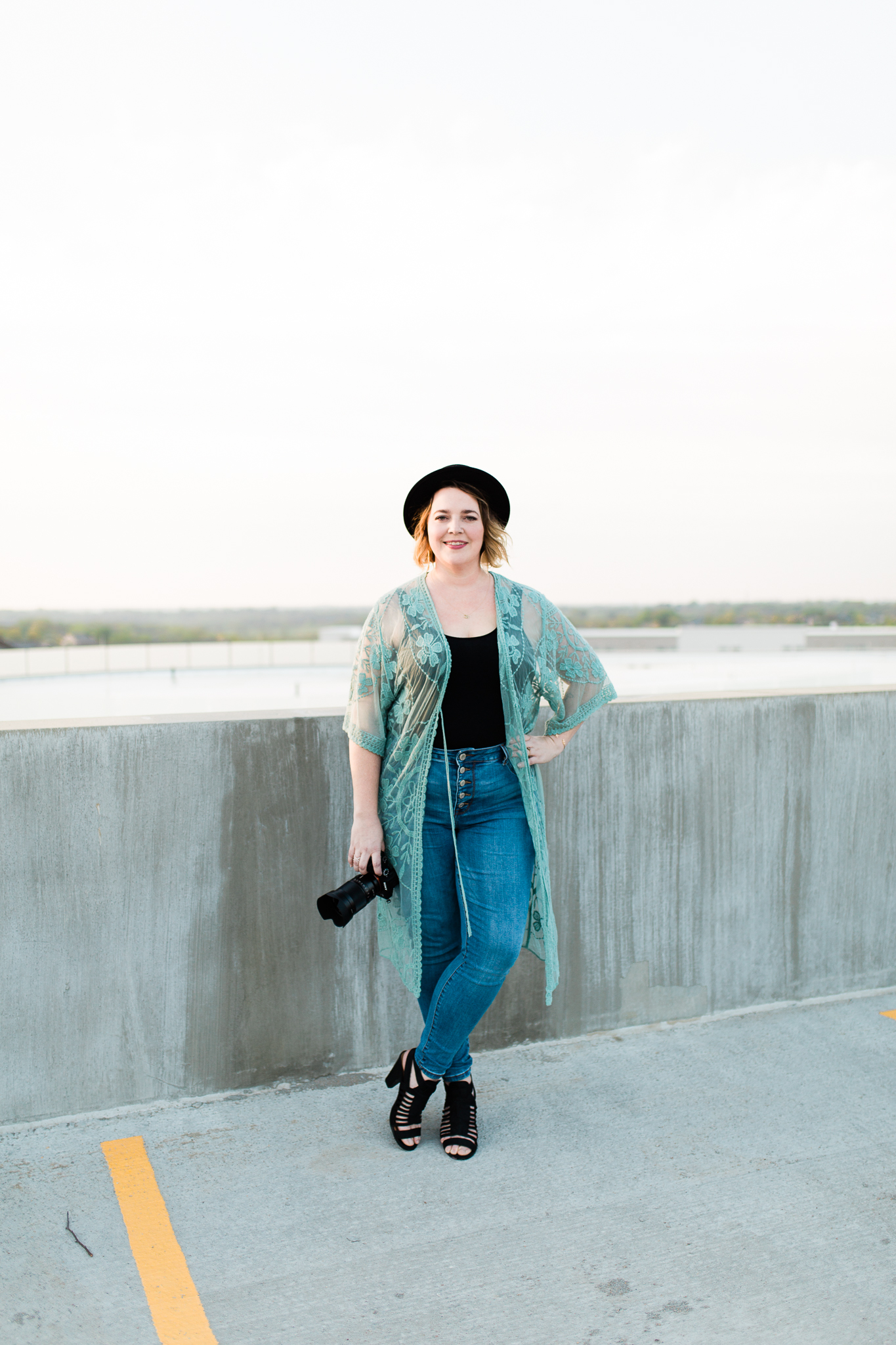 Photographer stands on a rooftop at sunset, Kansas City relaxed headshots, Rebecca Clair Photography