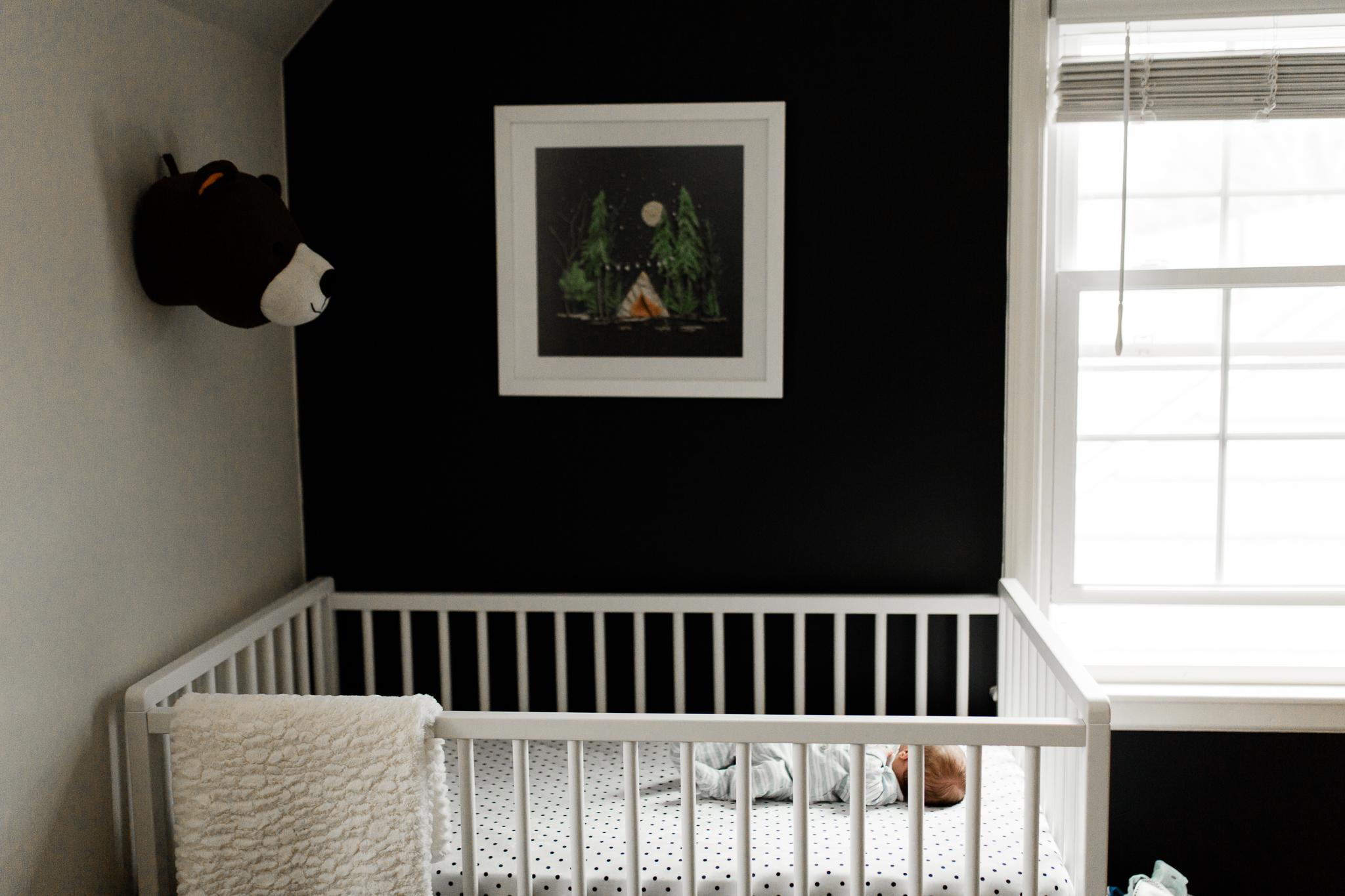Environment portrait of a newborn baby in his crib, camping themed nursery, Johnson County lifestyle newborn photographer