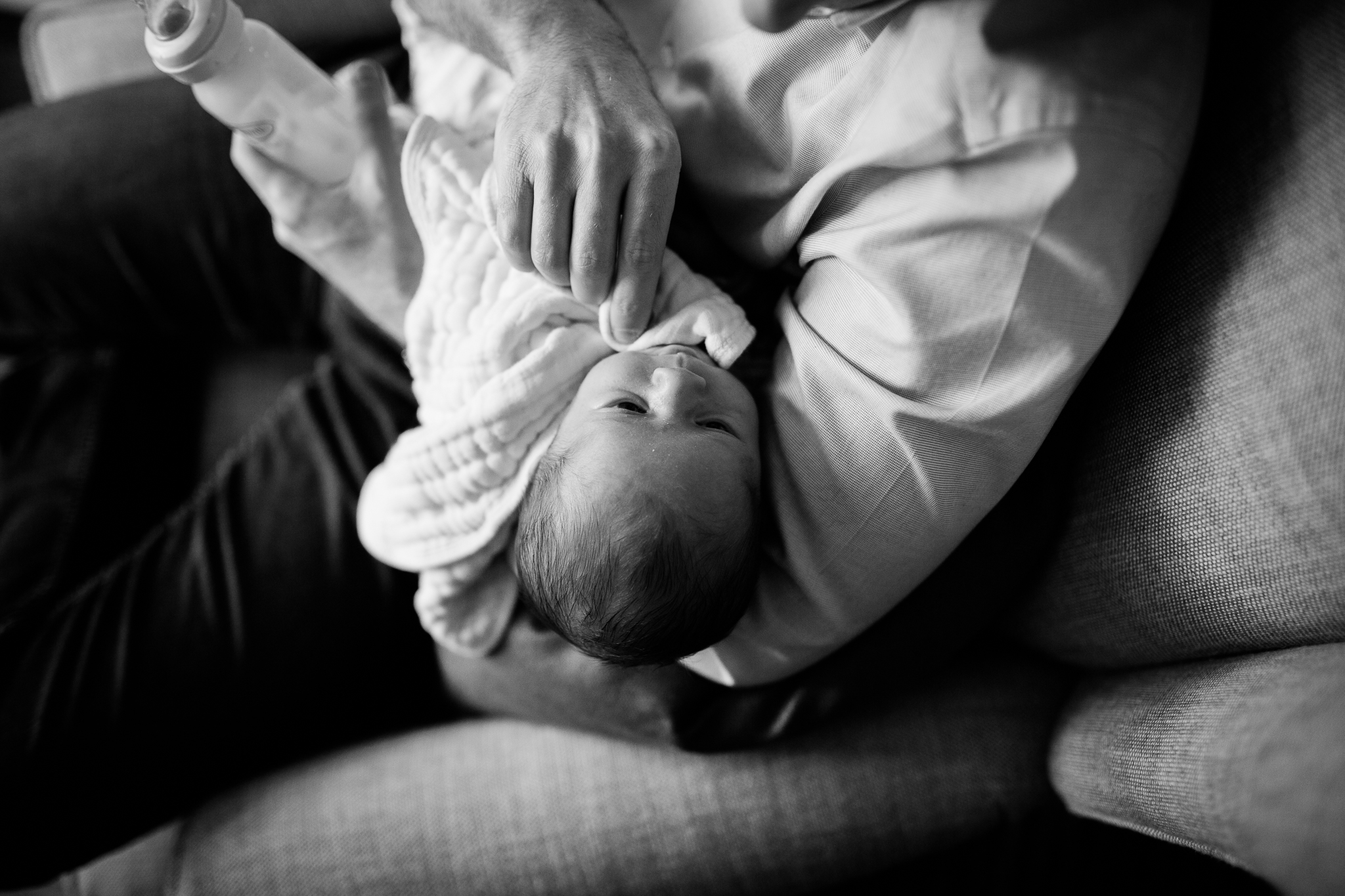 Black and white photo of father gently wiping his newborn son's face, Kansas City Johnson County emotive newborn photography, Rebecca Clair Photography