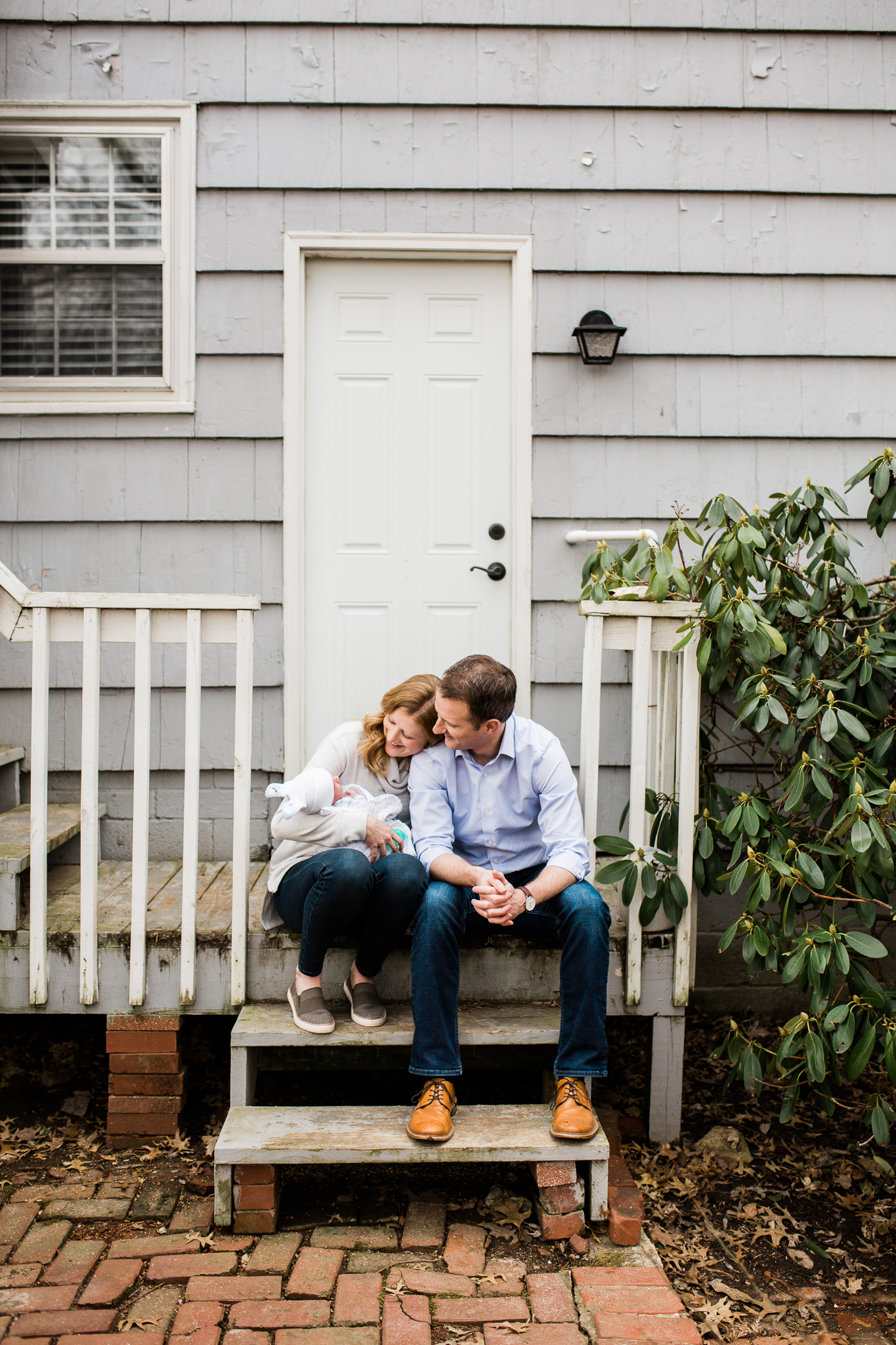 Parents cuddle their newborn baby on the back porch, Kansas City lifestyle newborn session, Rebecca Clair Photography