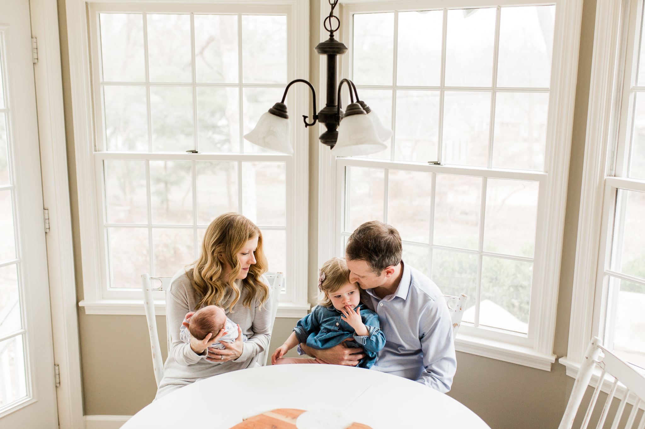 Family sits together in a light filled sunroom, Kansas City in home photo session, Rebecca Clair Photography