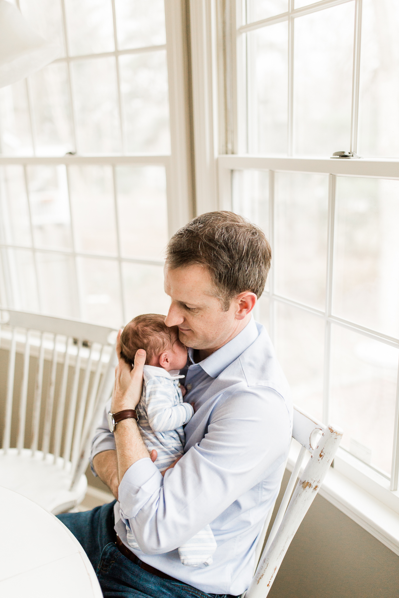 Father cuddles his newborn son in a light filled sunroom, Prarie Village lifestyle newborn photographer, Rebecca Clair Photography