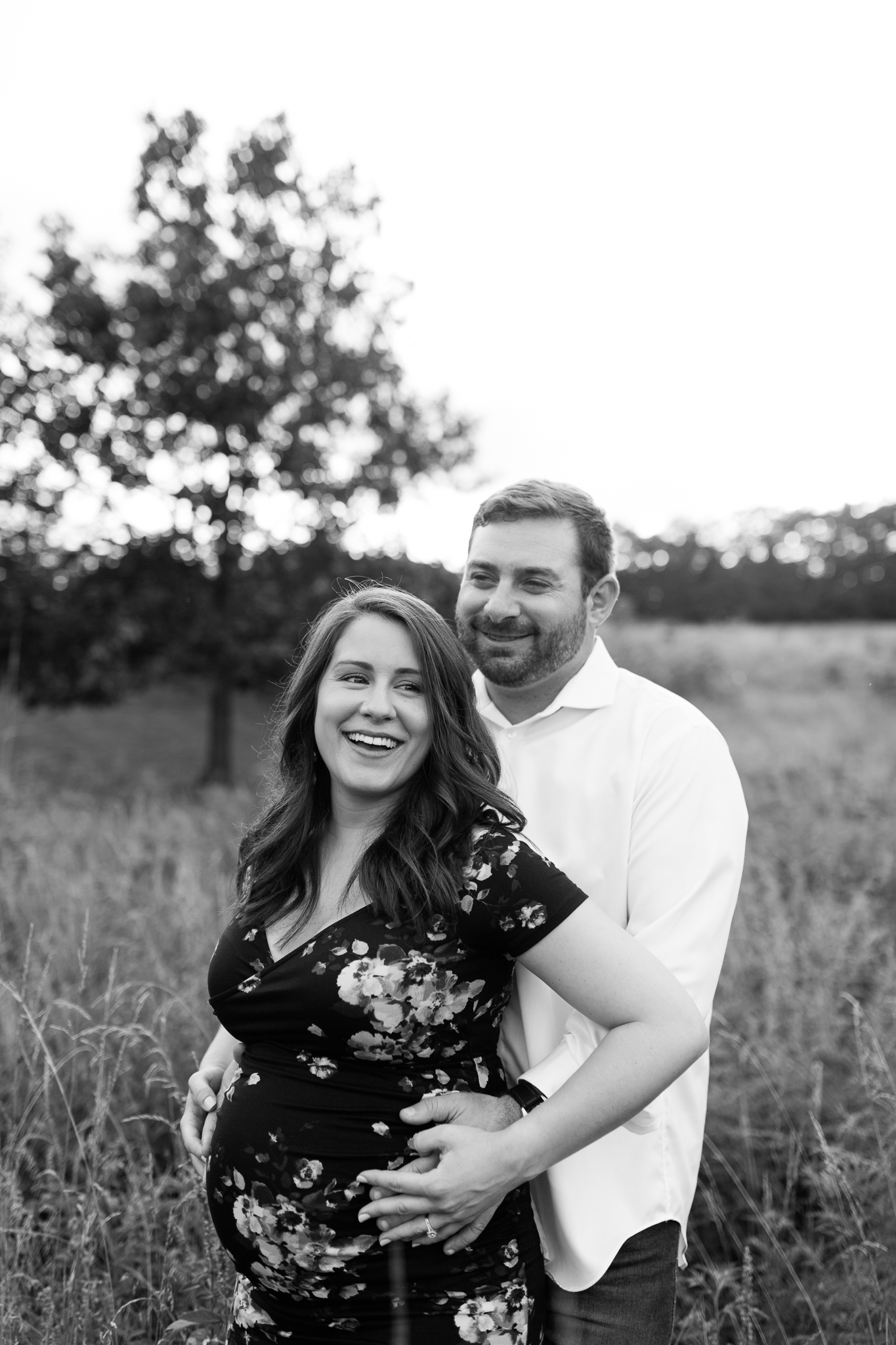 Black and white photo of pregnant couple laughing in a field, Rebecca Clair Photography, candid maternity photos in Johnson County, Kansas City maternity photographer