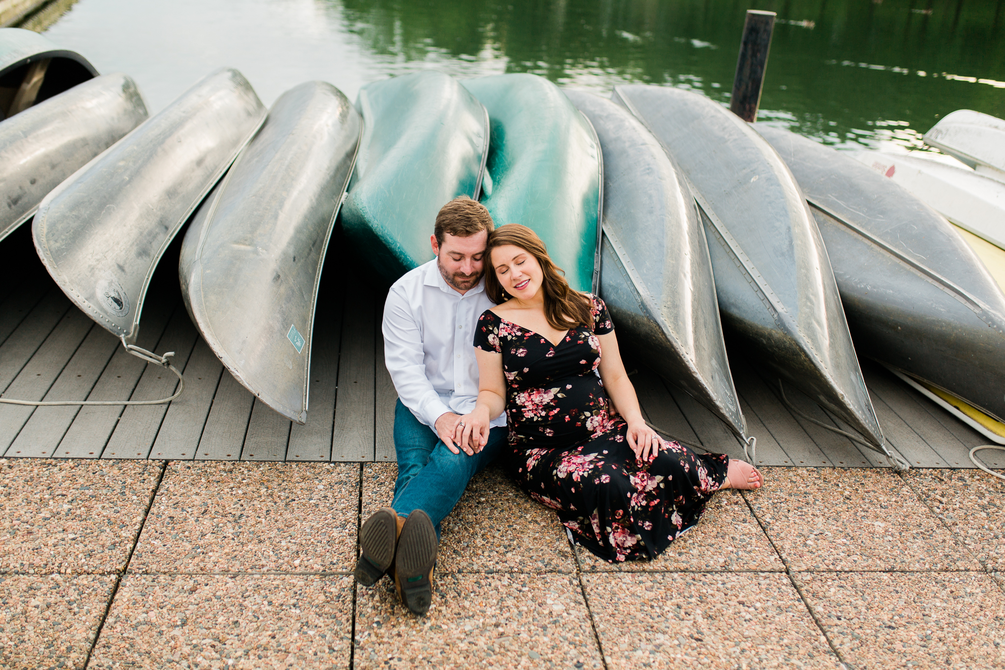 Pregant couple sit by a row of canoes, Shawnee Kansas and Johnson County maternity photographer, Rebecca Clair Photography