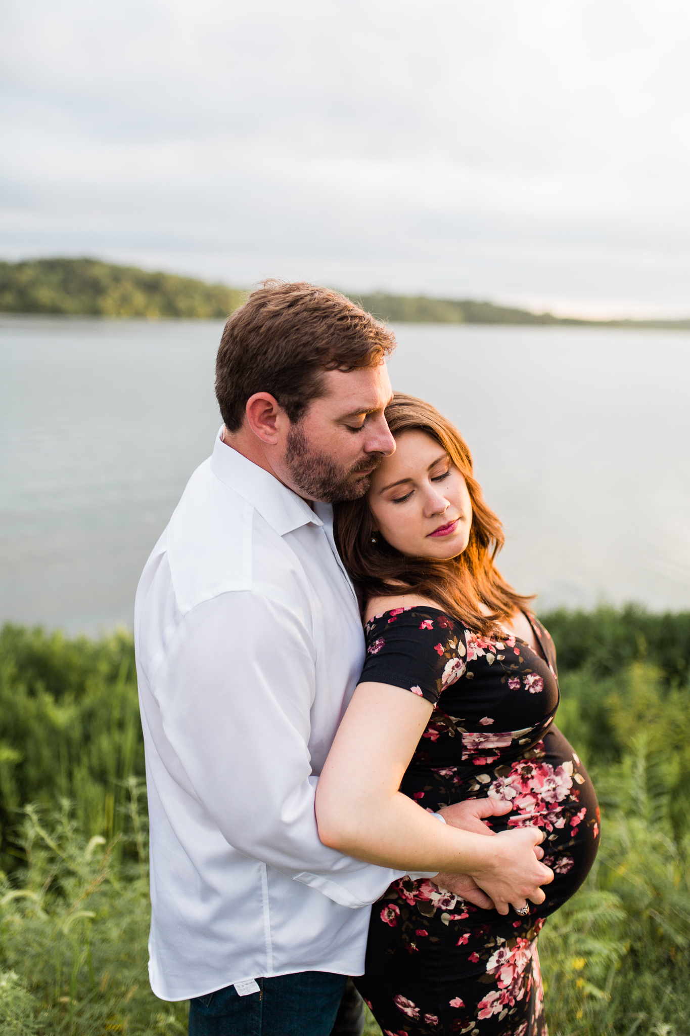 Pregant couple embraces by the lake, Kansas City sunset maternity session, Rebecca Clair Photography