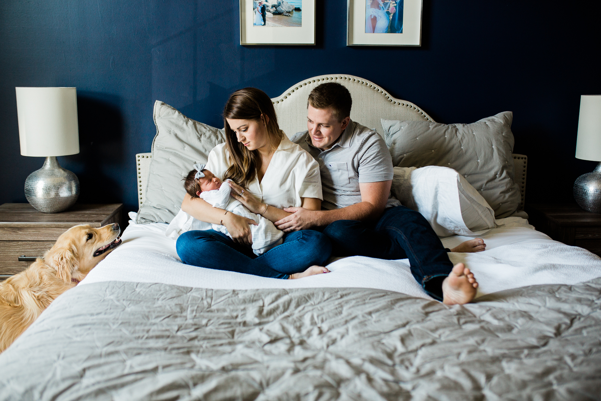 Couple cuddles their newborn baby on the bed while their dog watches, Overland Park and Johnson County lifestyle newborn photographer, Rebecca Clair Photography